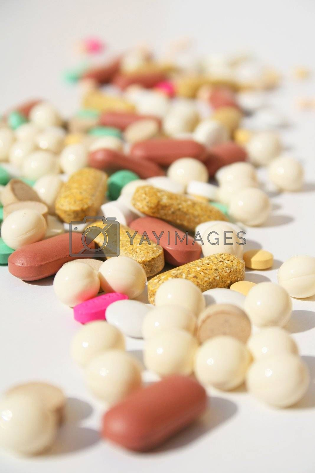 Various pills against white background with shallow depth of field on background