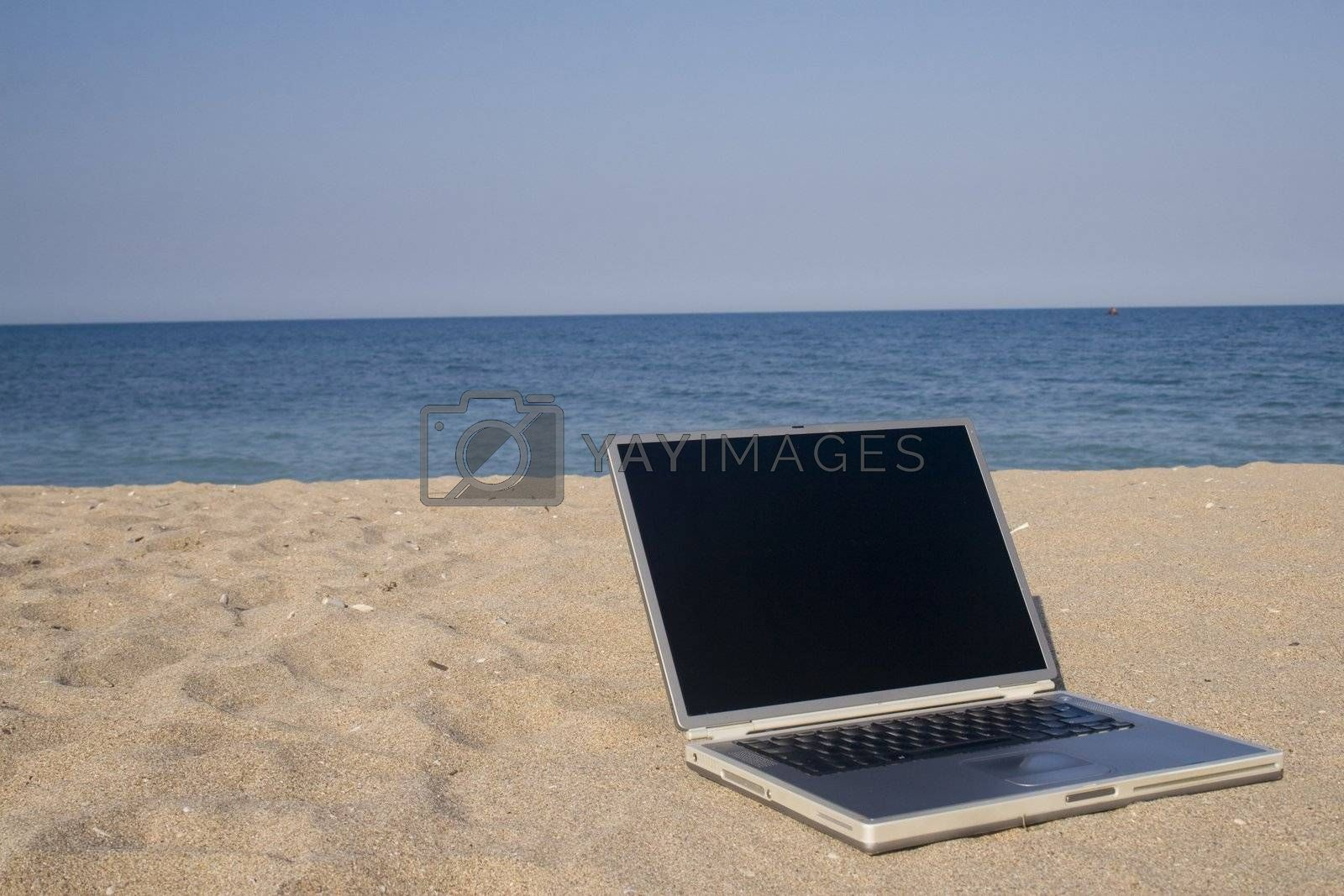 Laptop sitting on sand with sea and blue sky behind