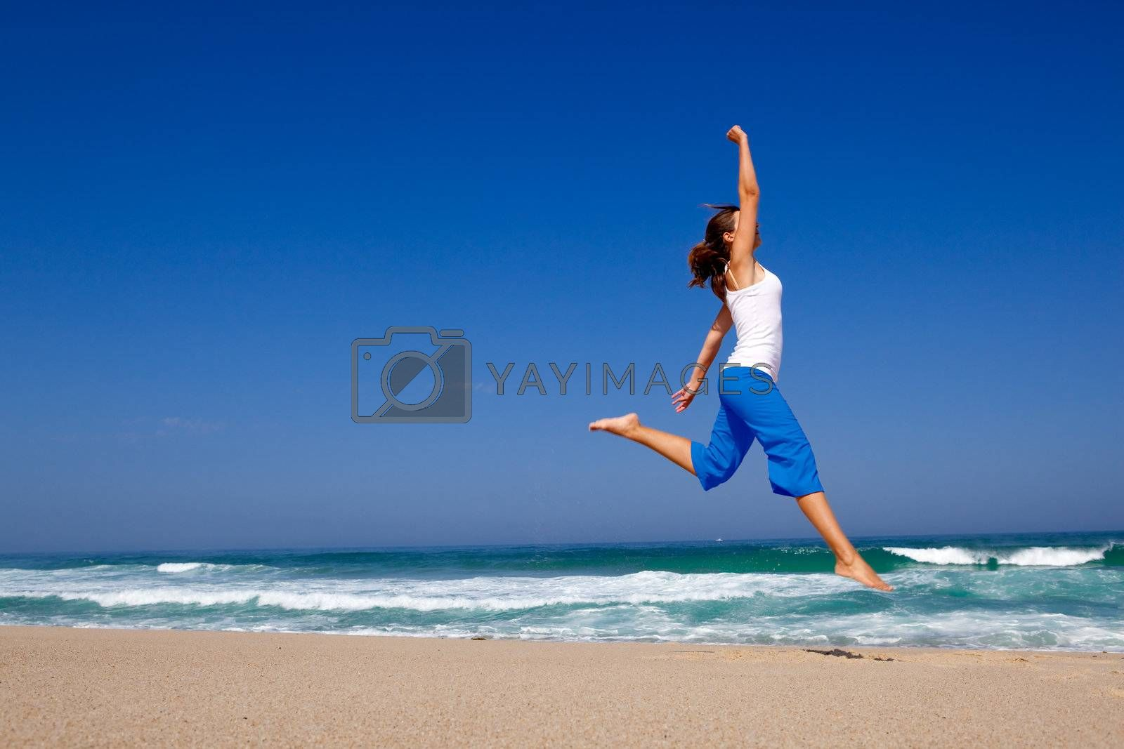 Beautiful young woman jumping on  the beach