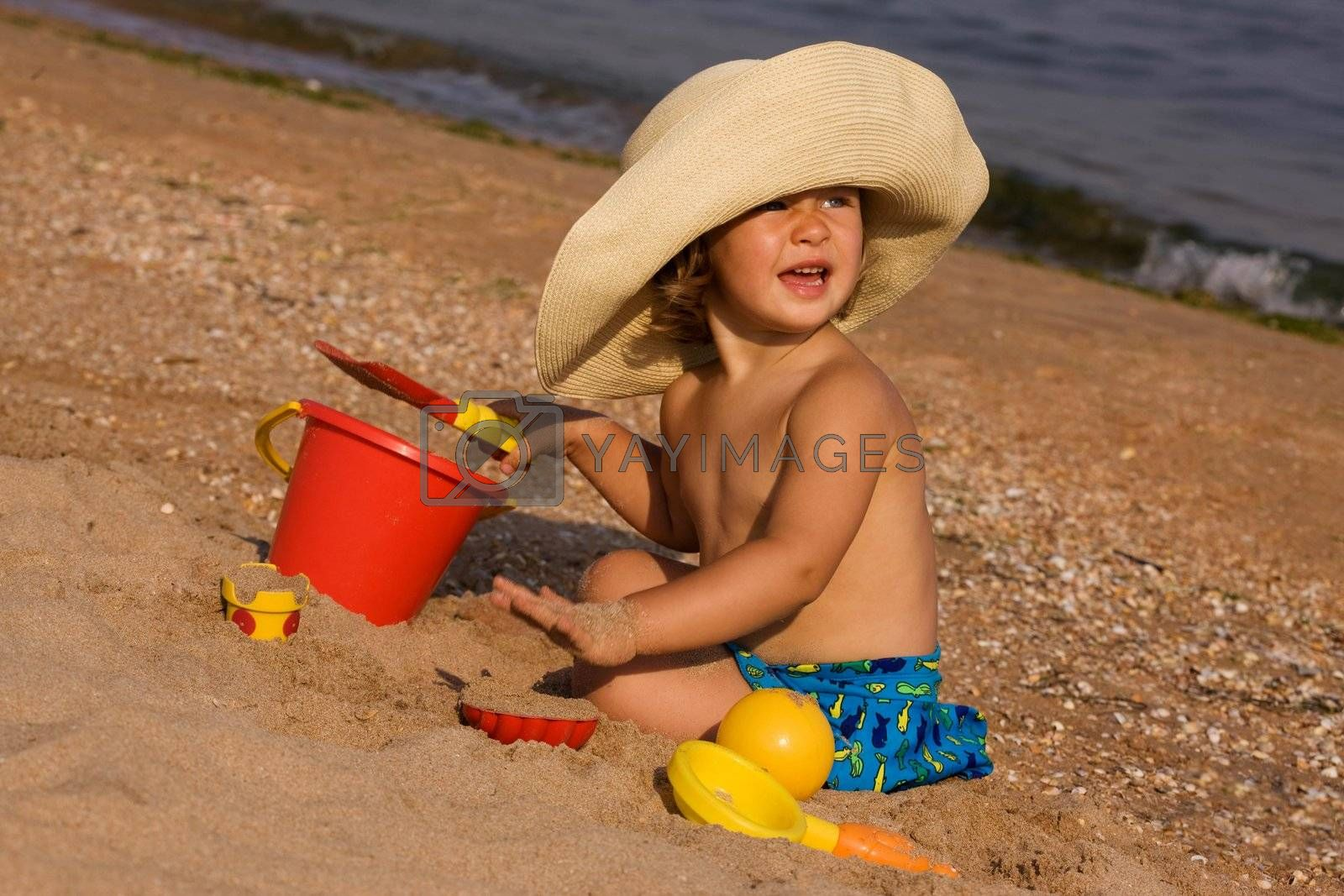 little girl in the bonnet plaing with sand, happy childhood