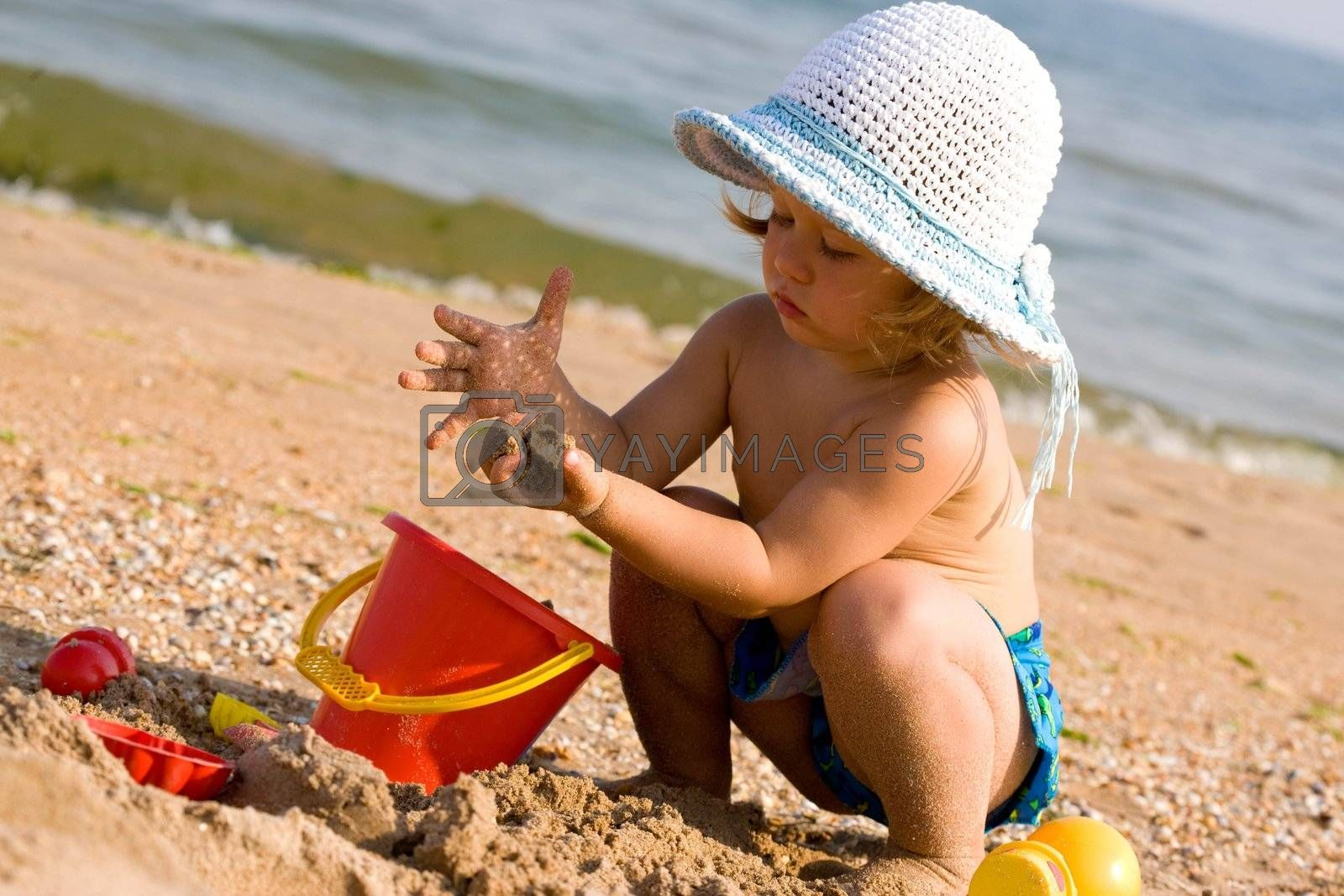 little girl in the bonnet plaing with sand, childhood