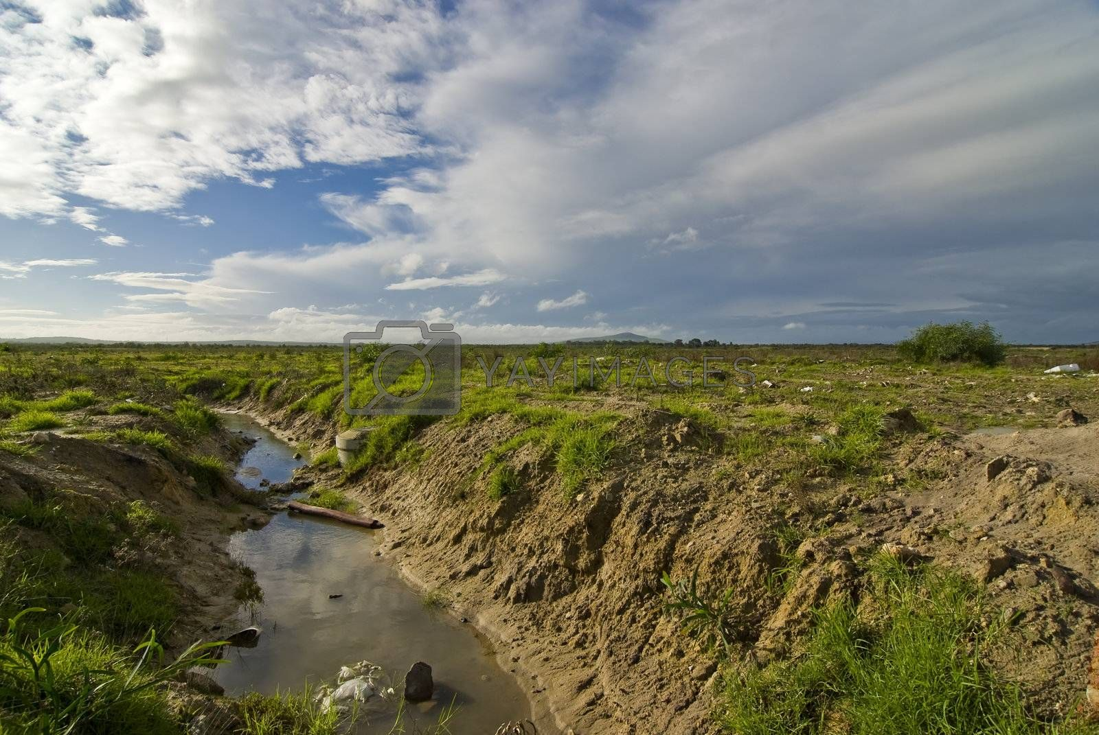 Polluted stream and landscape with patches of green and blue skies and white clouds overhead