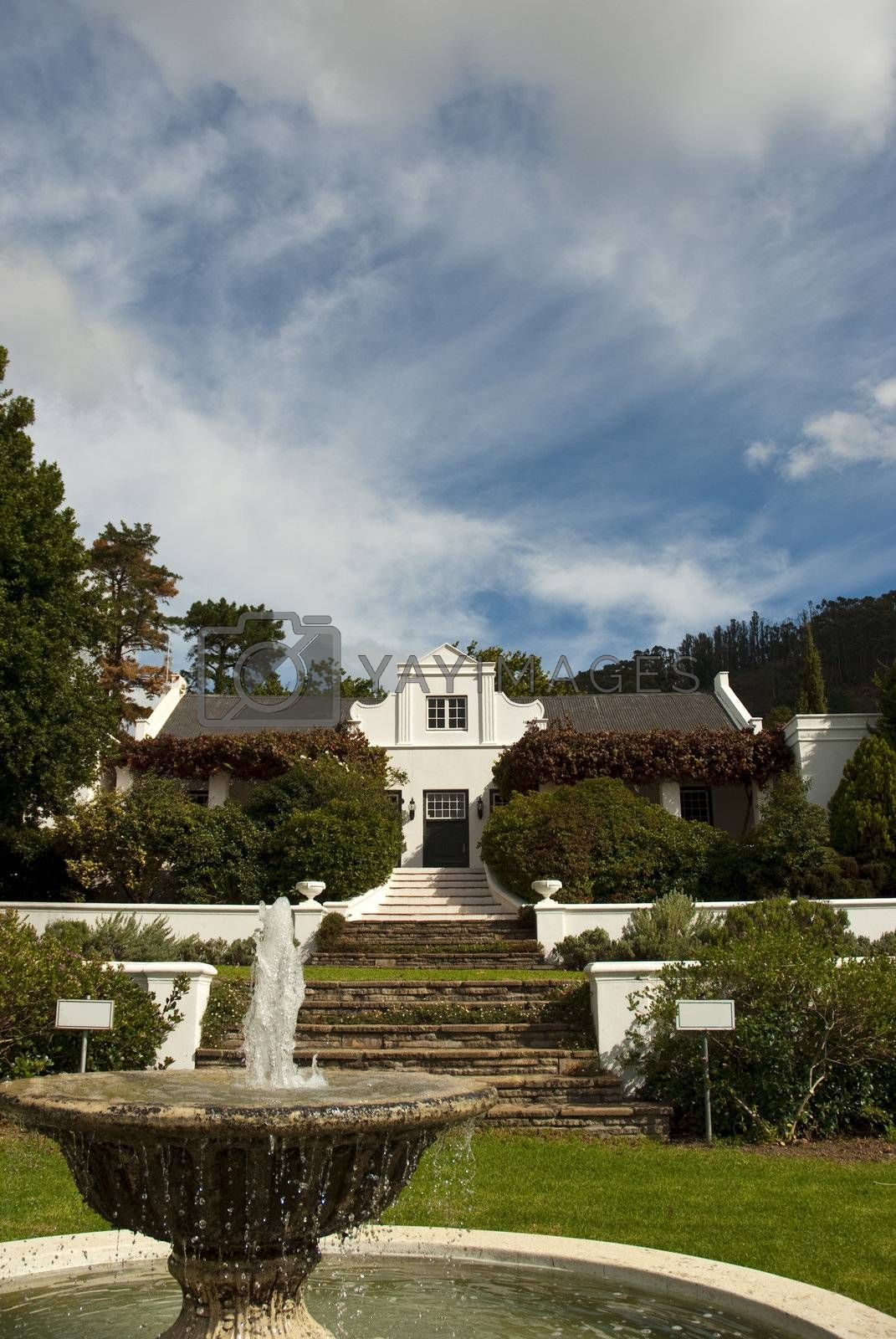 Classic Cape Dutch farm house with garden in the foreground and cloudy blue skies overhead