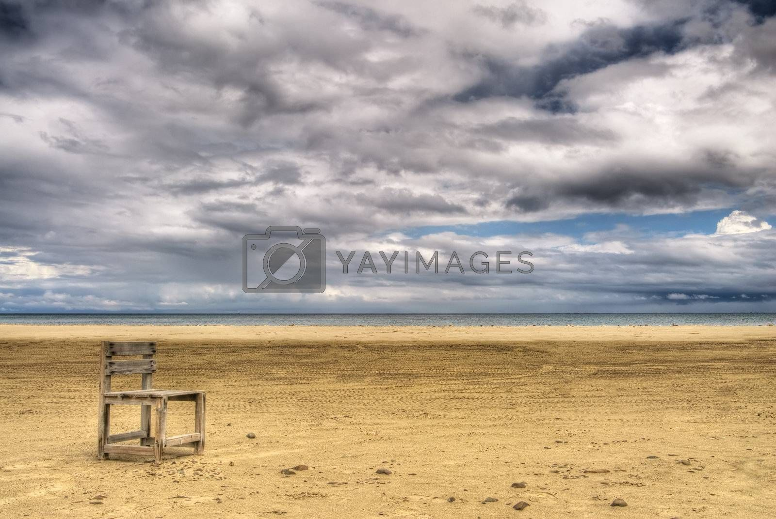 Alone scenic with single chair on yellow sand under white dramatic  clouds in sky.