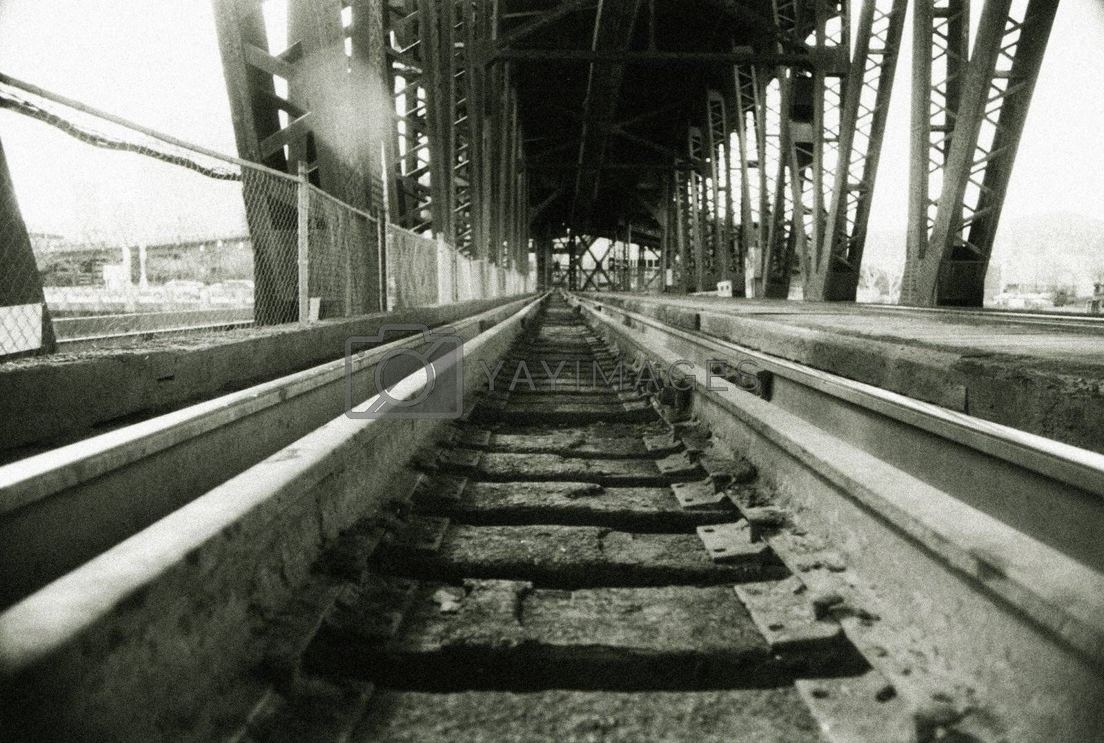 Railroad tracks on bridge disappearing into horizon