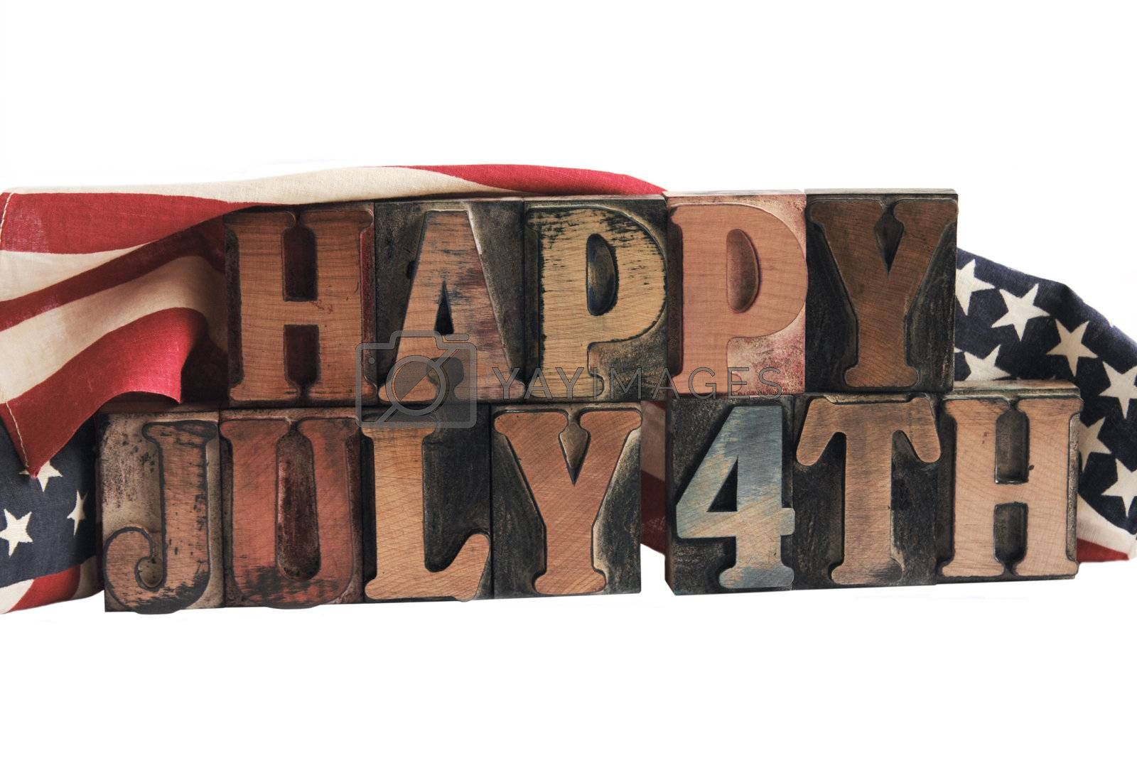 the phrase 'happy July 4th' in ink-stained letterpress type with flags draped behind