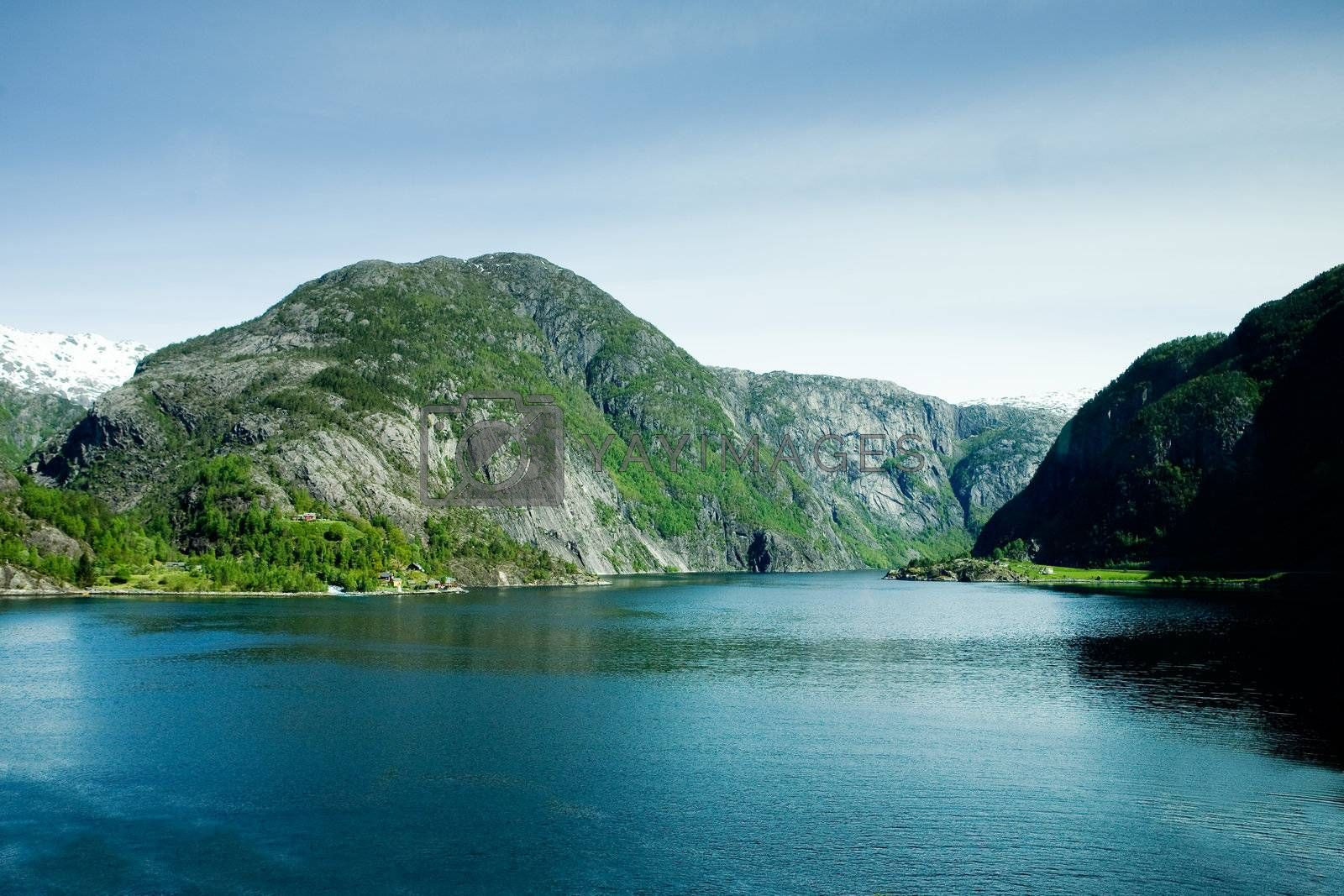 A fjord and rural norway with a blue sky
