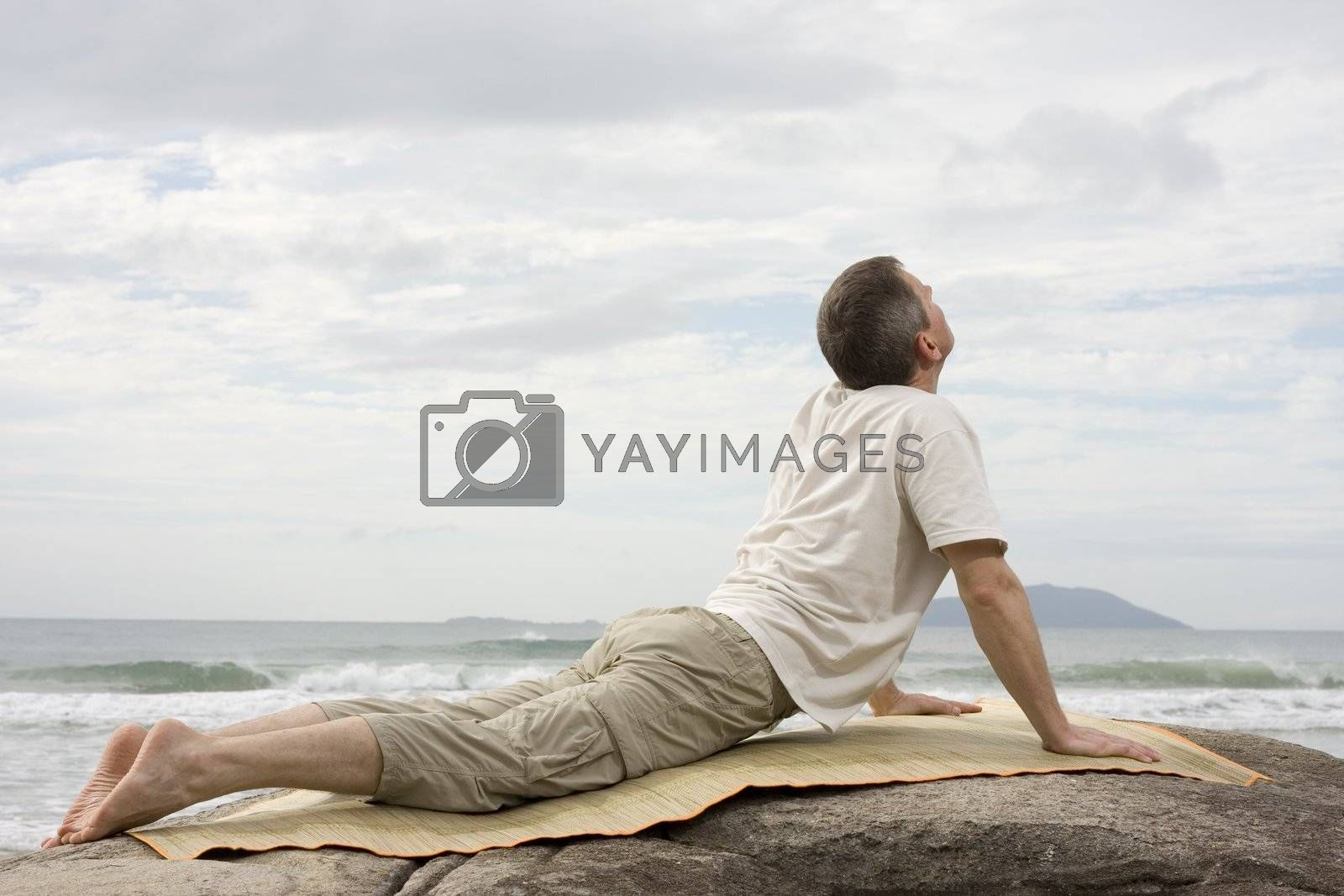 Mature man doing yoga at the sea by ArtmannWitte