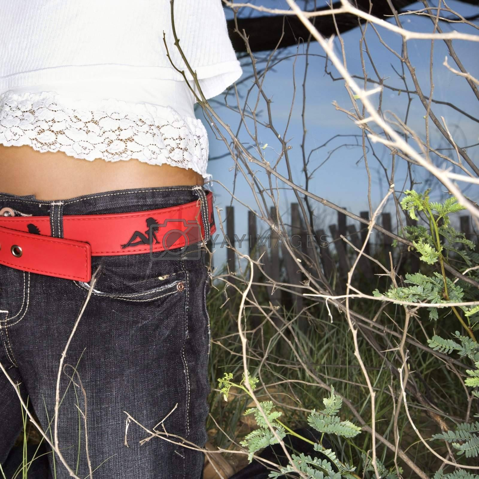Young adult Asian female torso with red belt outside.