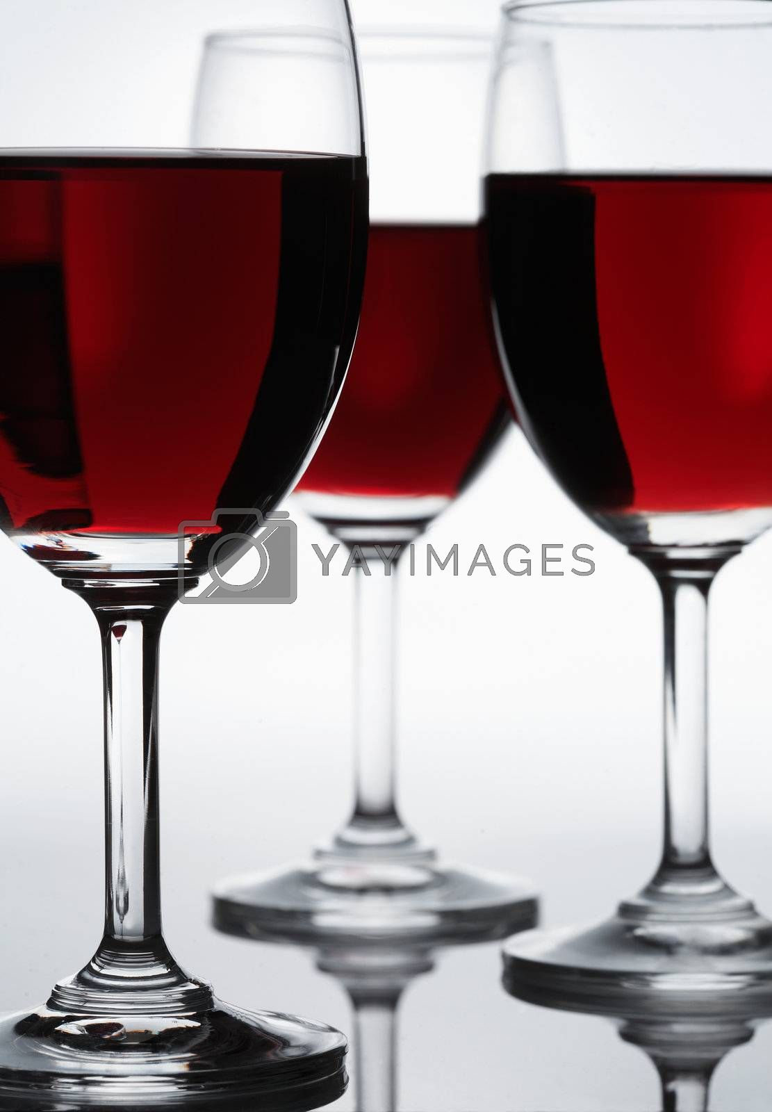 Three glasses of red wine. Focus is on the first glass.