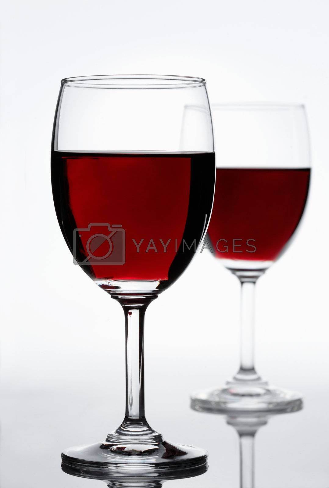 Red wine on white background. Focus is on the first glass