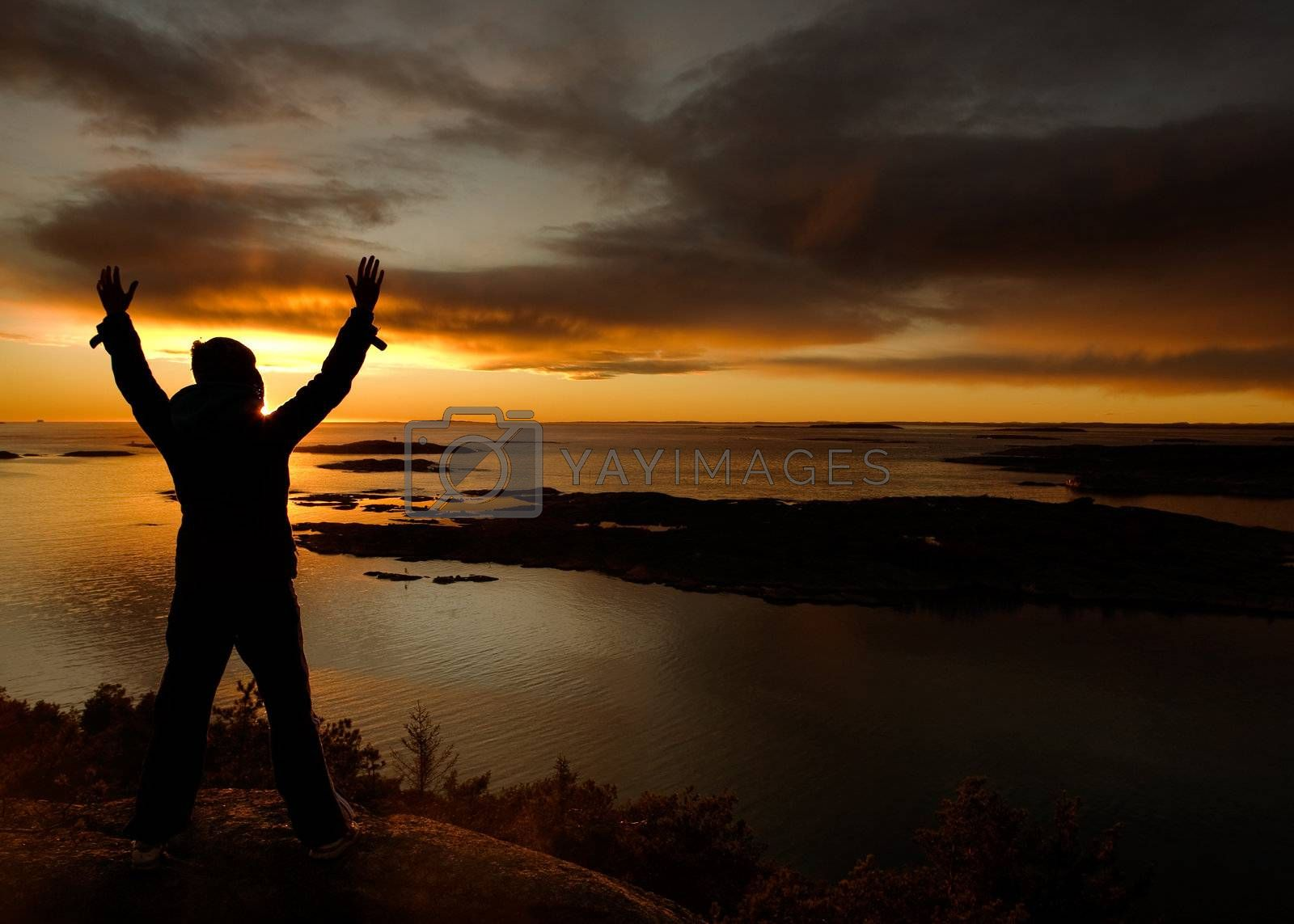 A person standing by the ocean raising their arms in celebration