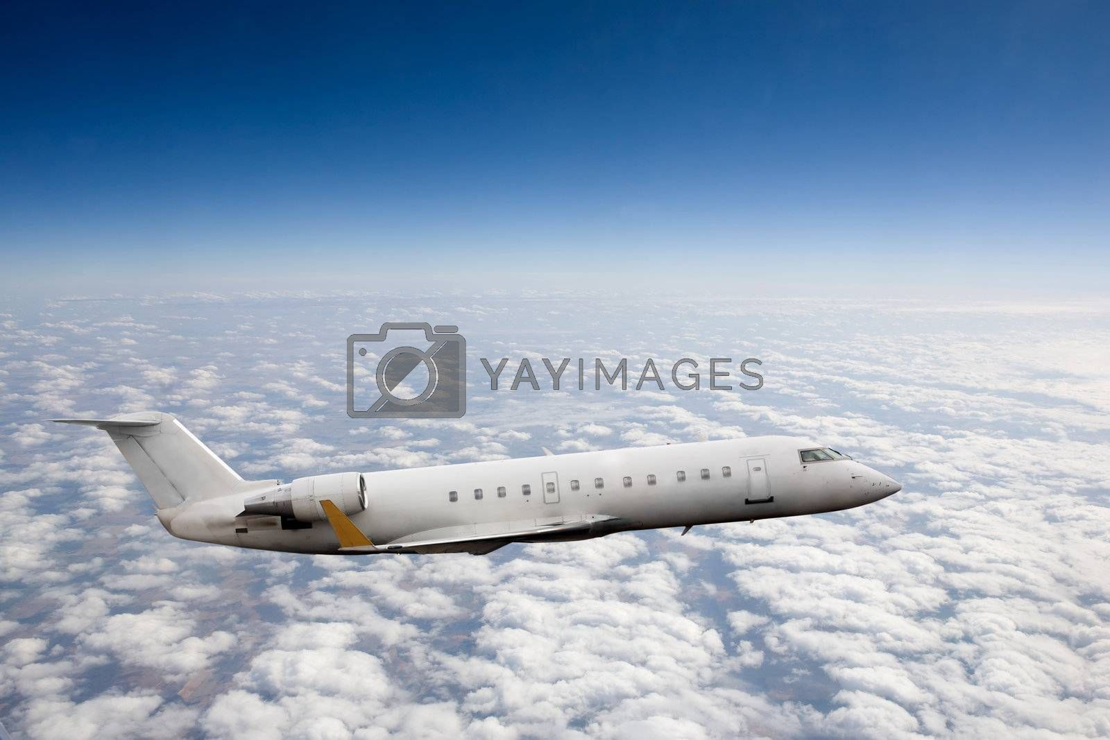 Airplane in flight over high altitude clouds