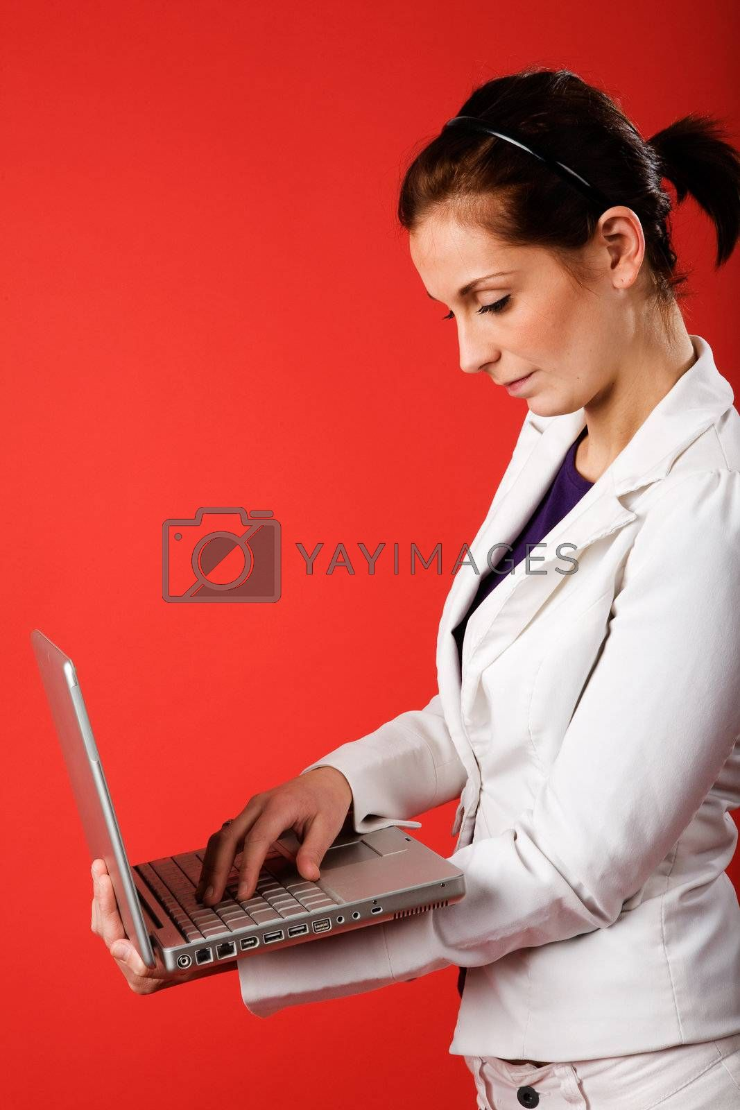 A young business woman or student using a laptop with a strong red background