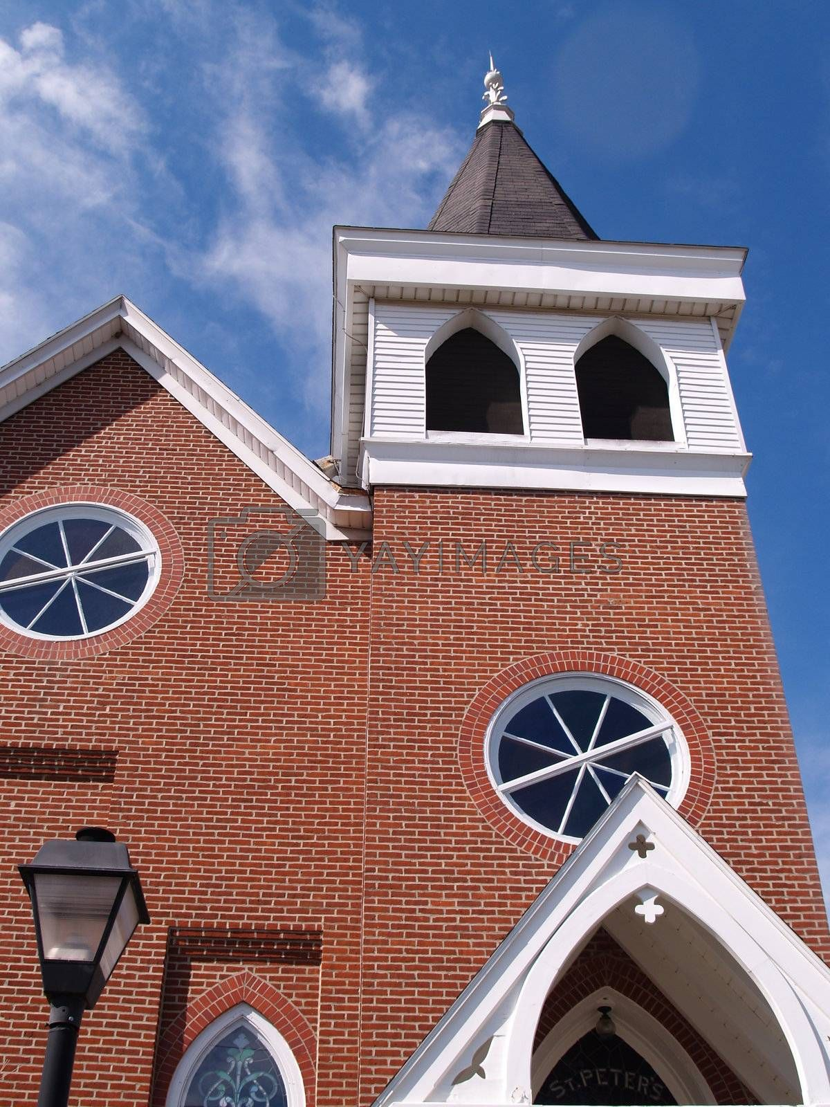 exterior of a red brick church with bell tower and steeple