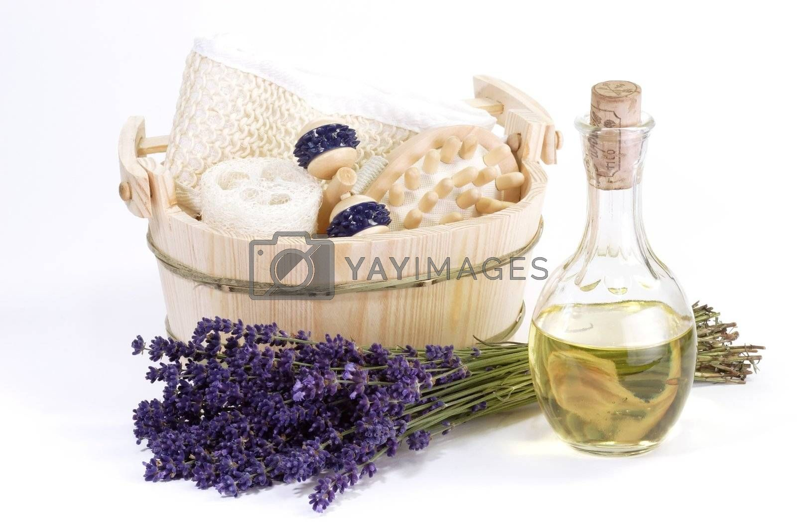 Massage supplies, bunch of lavender and bottle of oil on white background