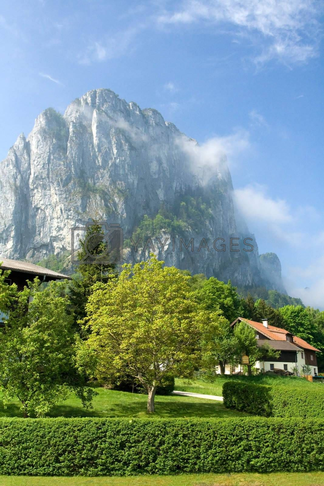 Tranquil spring countryside at the foot of foggy rock on the blue sky background