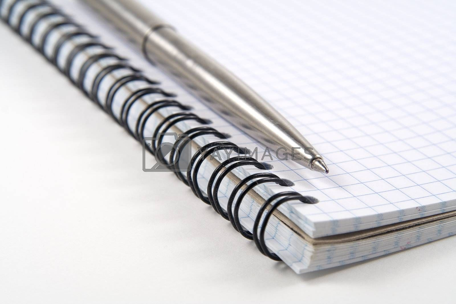Pen on spiral notebook on white background by serpl