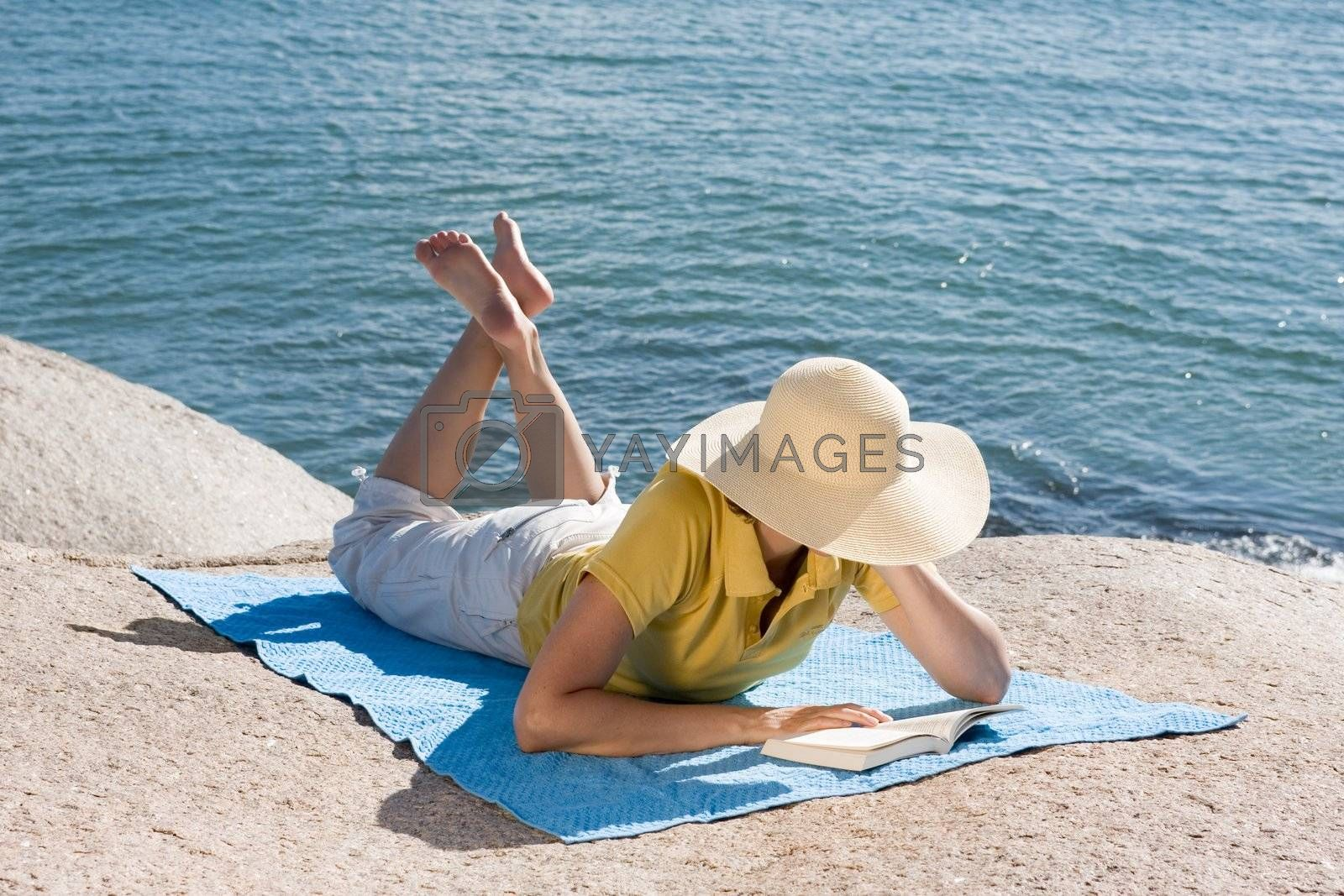 Woman reading a book while lying on a rock at a beach