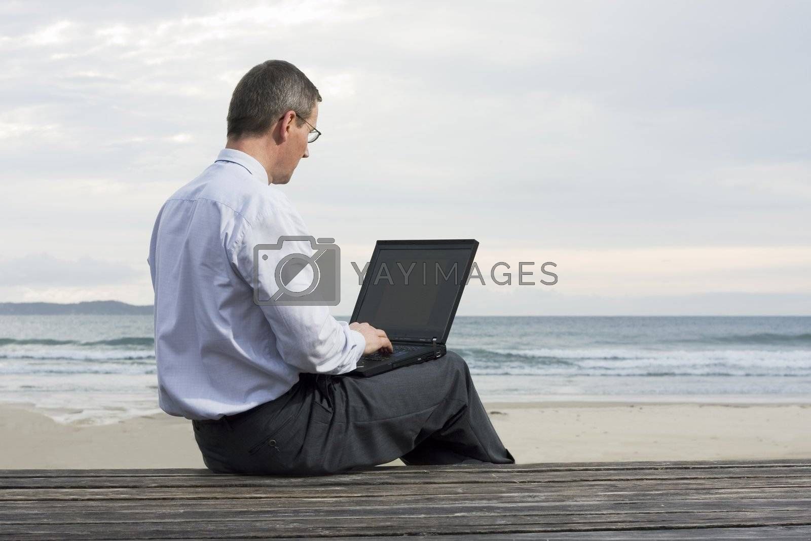 Businessman working with laptop on a beach by ArtmannWitte