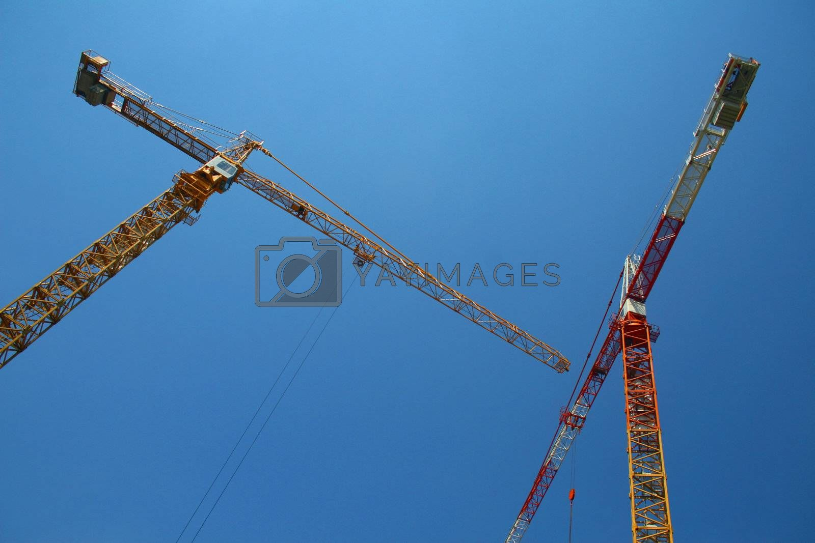Two building cranes against cloudless sky