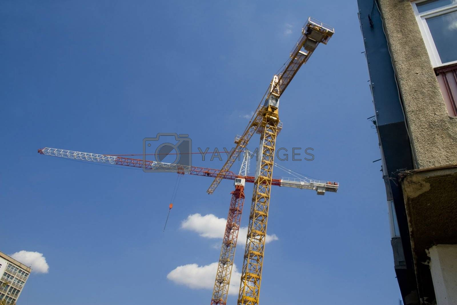 Two cranes with old apartment building to right of frame