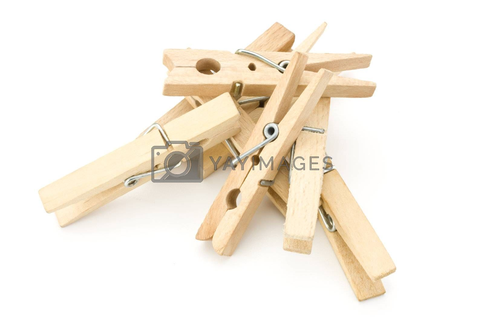 a heap of wooden clothespins on white background