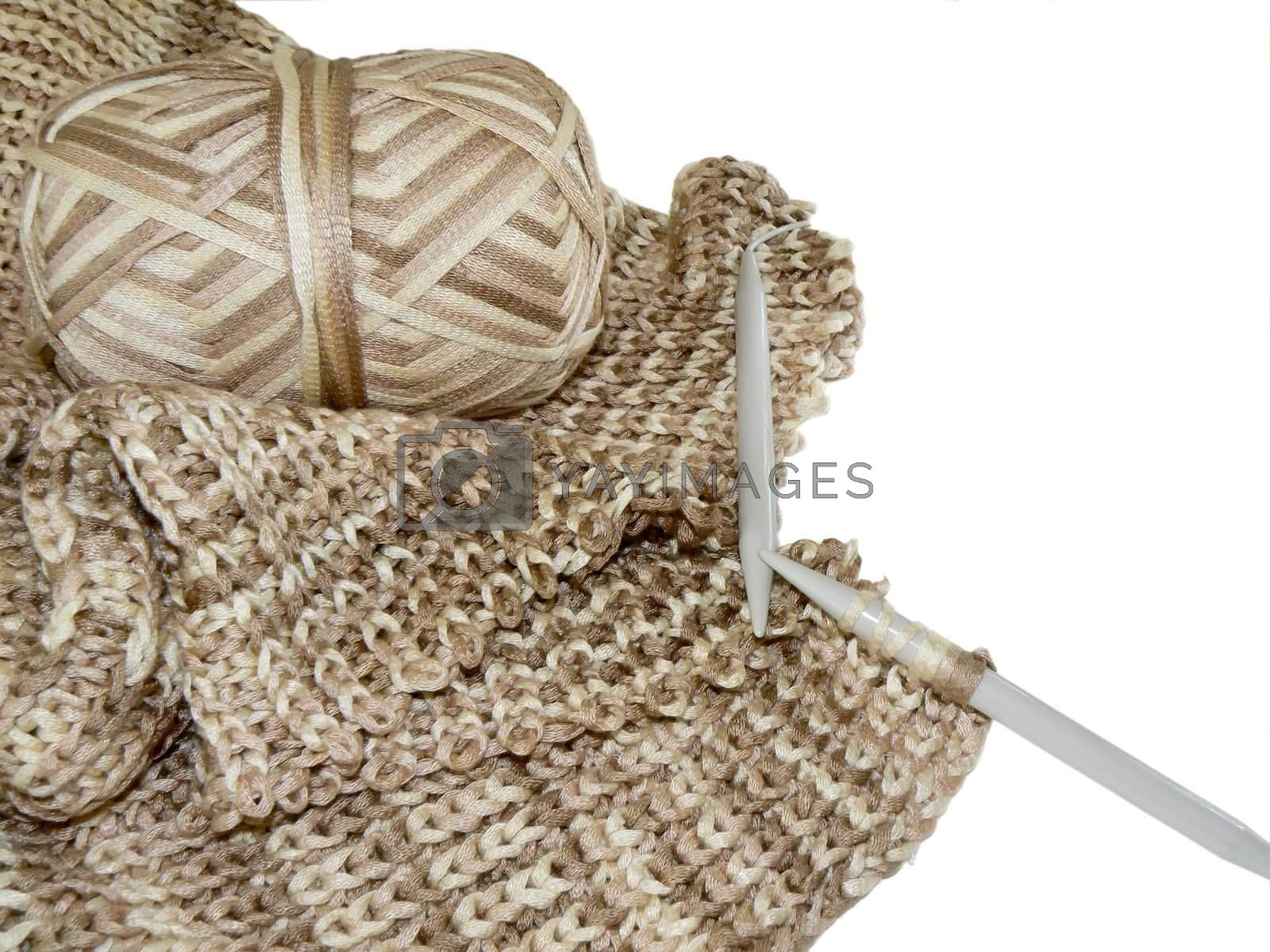 Part of woolen sweater, yarn and spokes on white