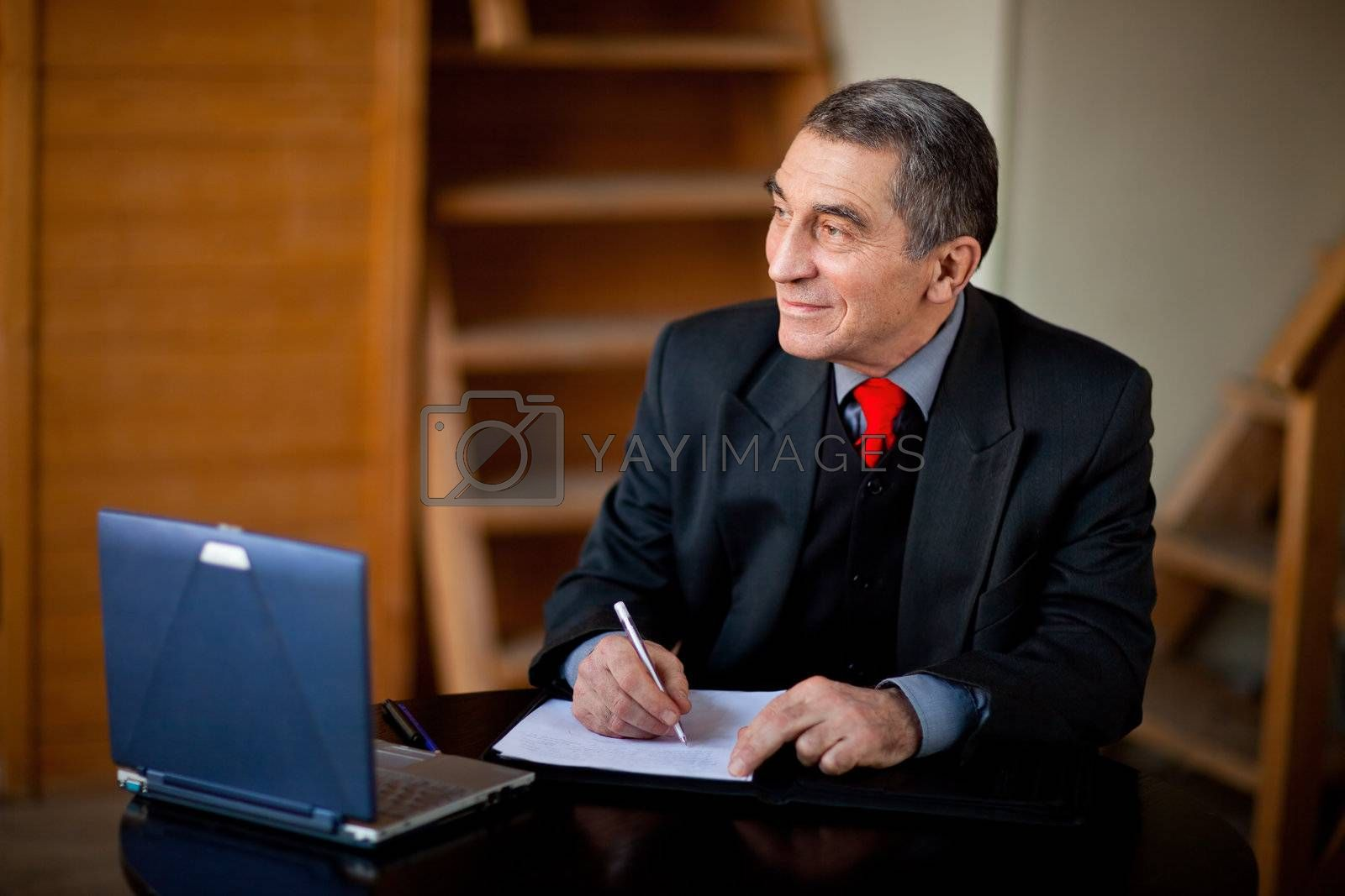 Senior businessman writing and working with document indoors