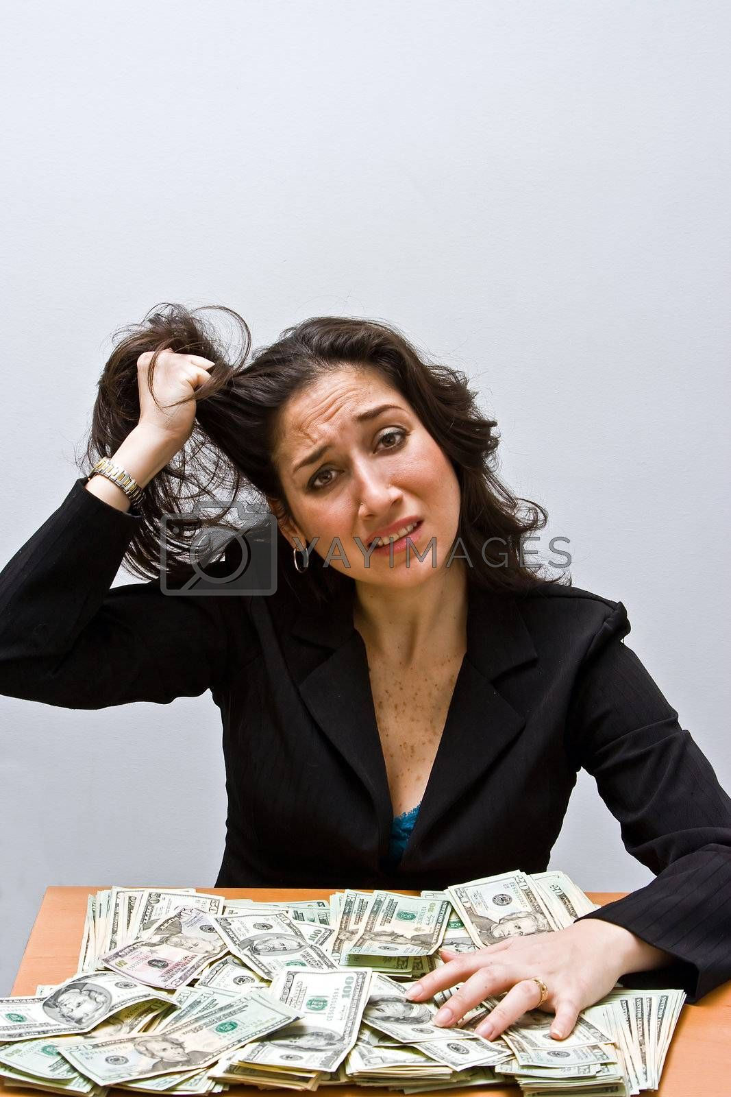 Business woman pulling hair and stressed about finances. Sitting at a table with lots of money. Isolated on a white background