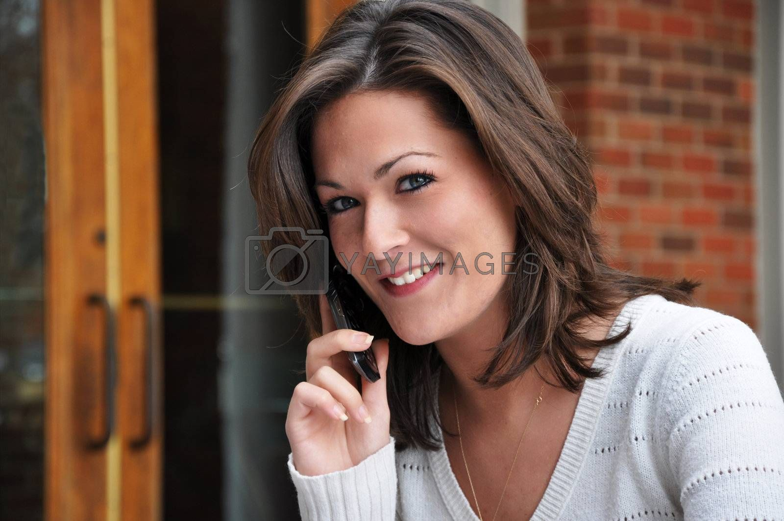 Closeup of young woman talking on cell phone and looking at camera.
