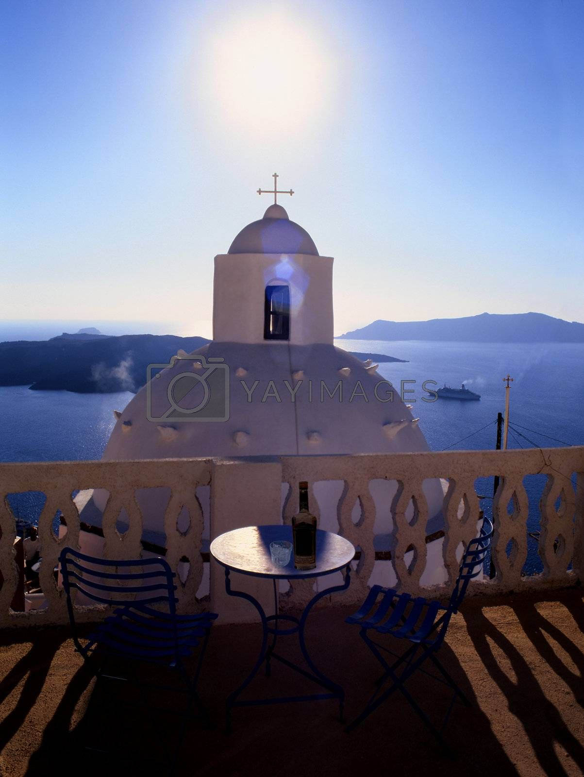 A balcony overlooking a small church on the Greek island of Santorini,  with the sun setting directly in front blue sky and mountains in the background.