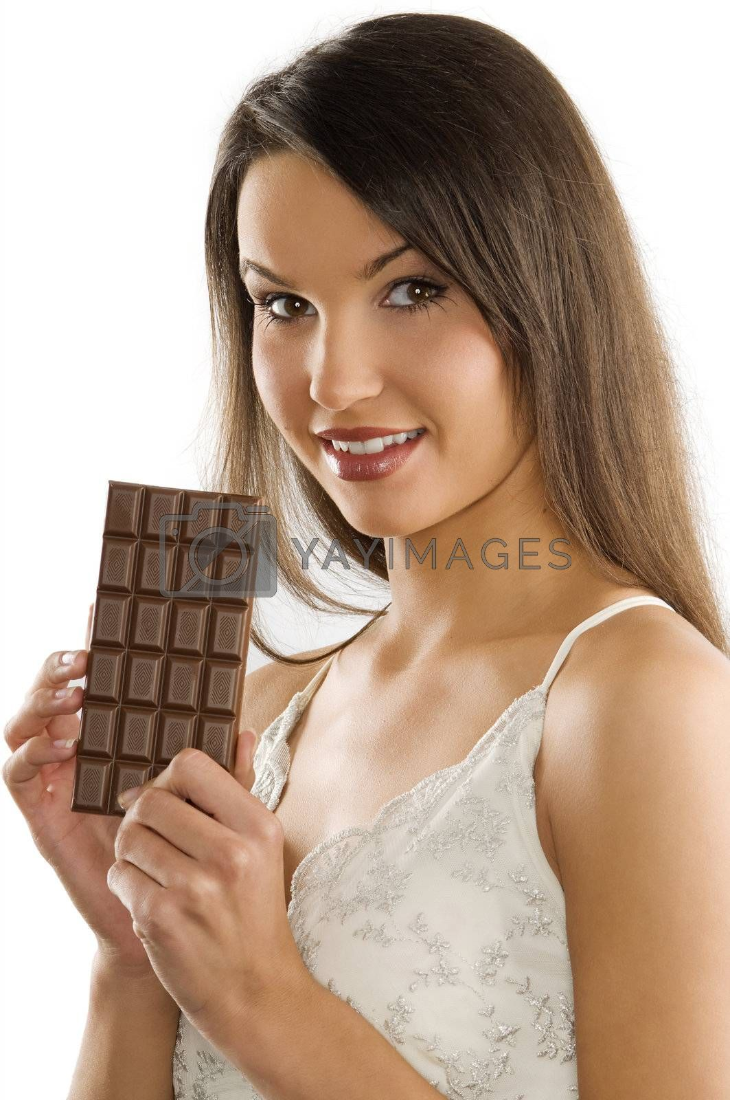 brunette in white dress showing a block of chocolate smiling