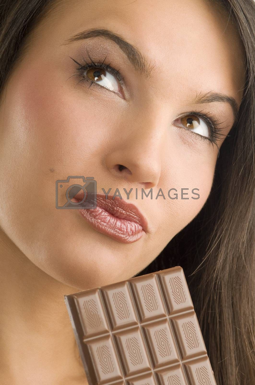 close up of a young and beautiful girl looking up and having a block of chocolate