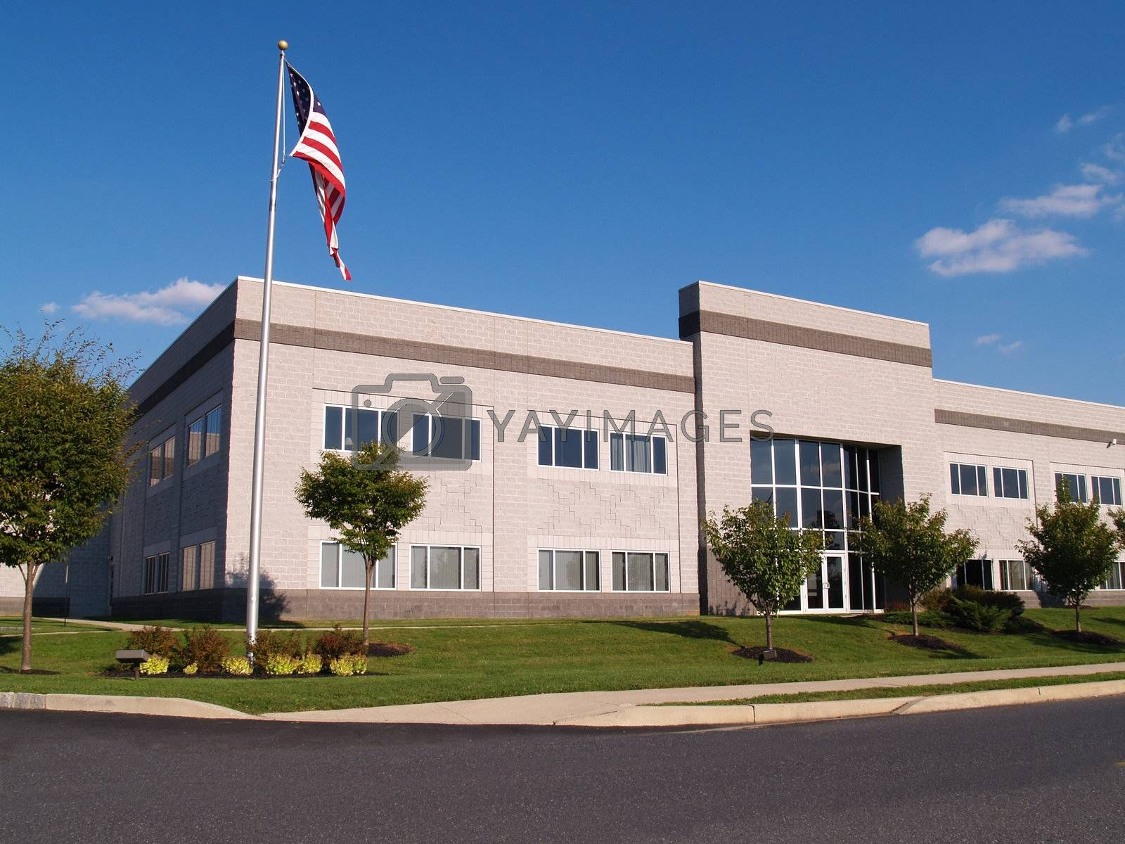 exterior of a modern industrial building with the American flag on flagpole