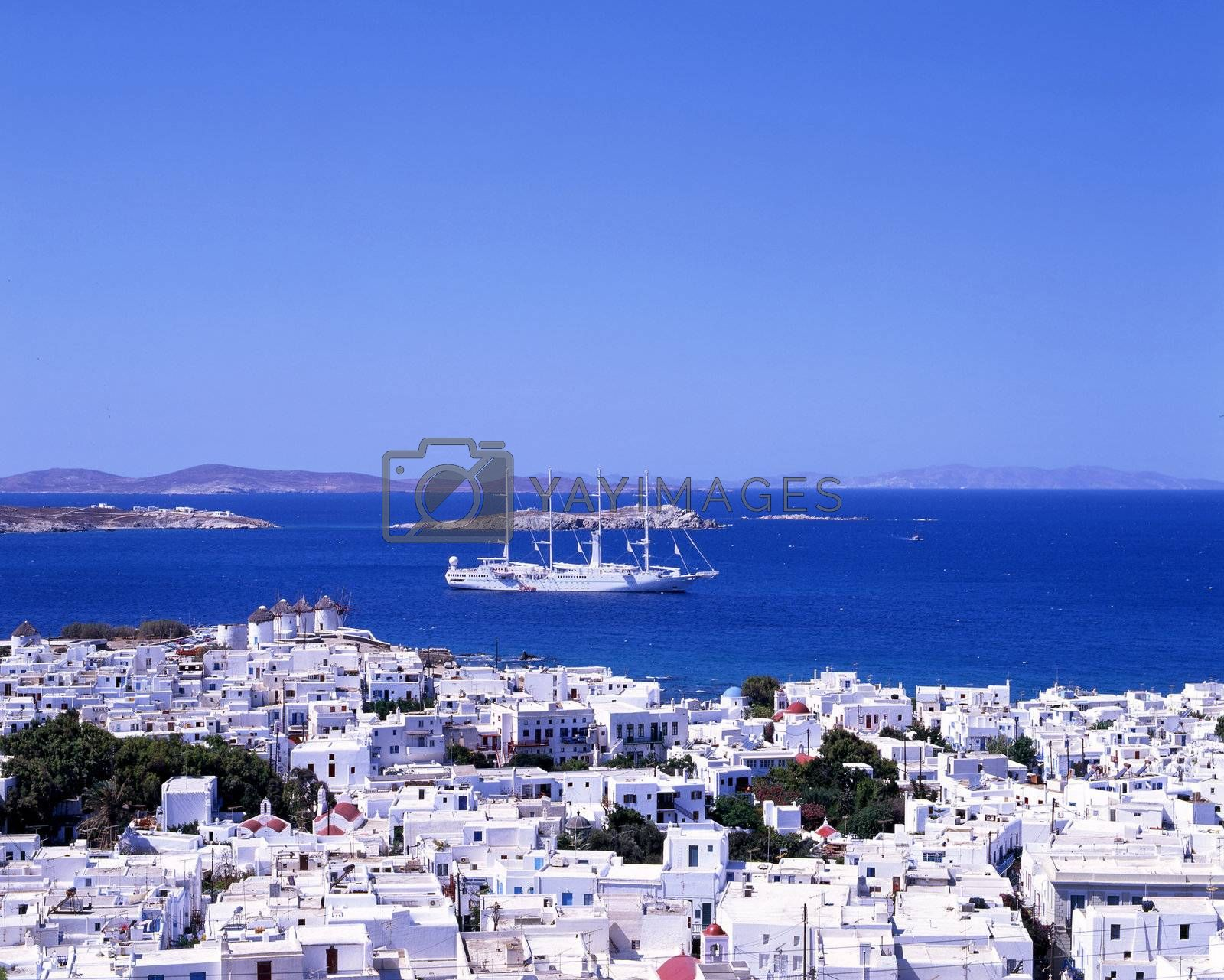 A large white sailing boat going into the port of Mykonos, a Greek island