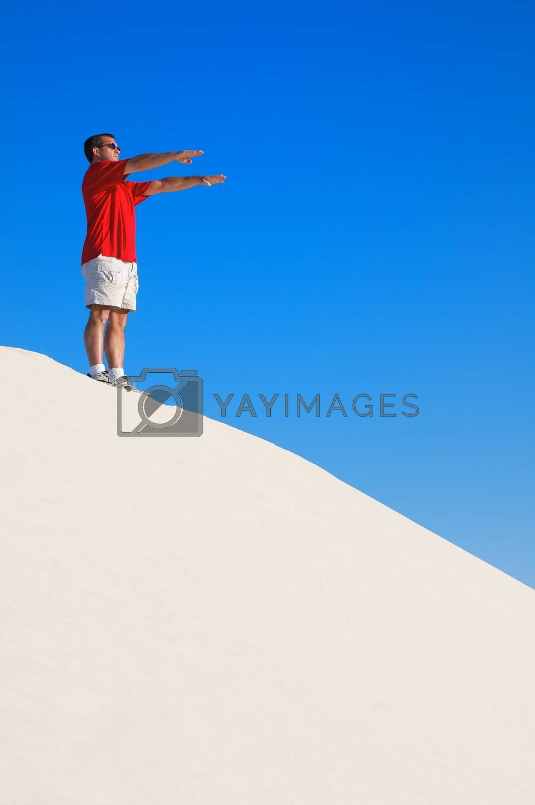 Man in a red shirt with his arms raised in a yoga pose looking off into the distance on top of a white sand dune with a blue sky