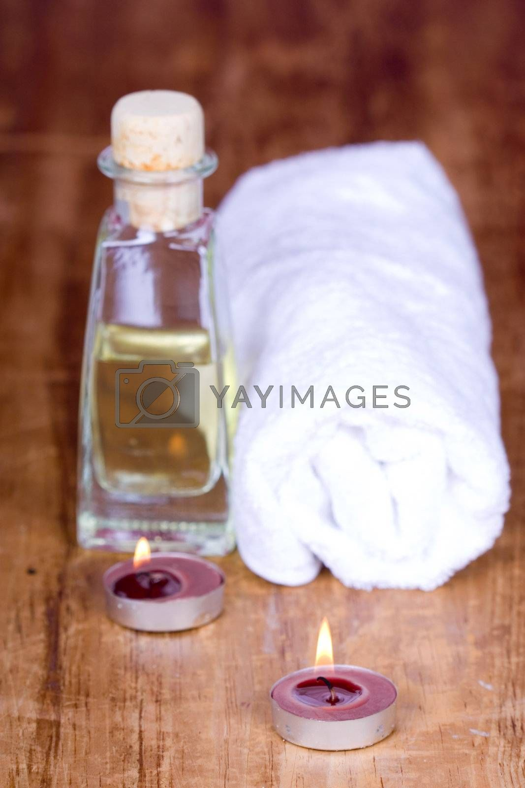 spa products (towel, oil, candles) on wooden background