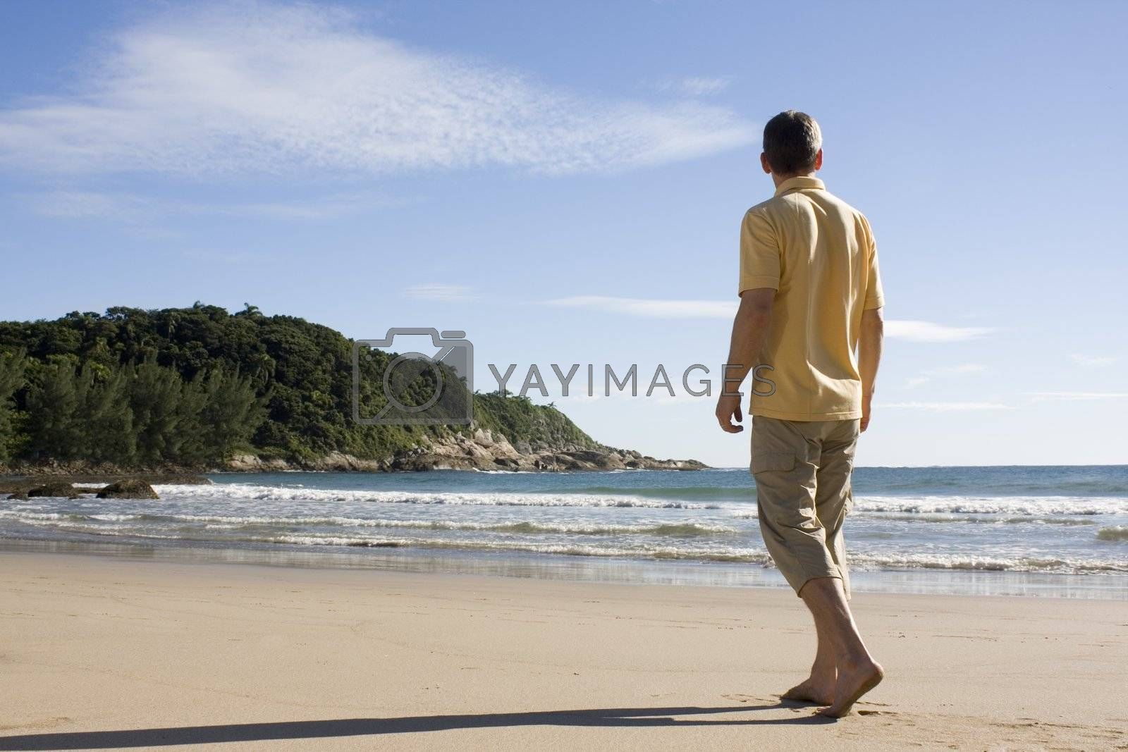 Royalty free image of Man walking barefoot on a tropical beach by ArtmannWitte