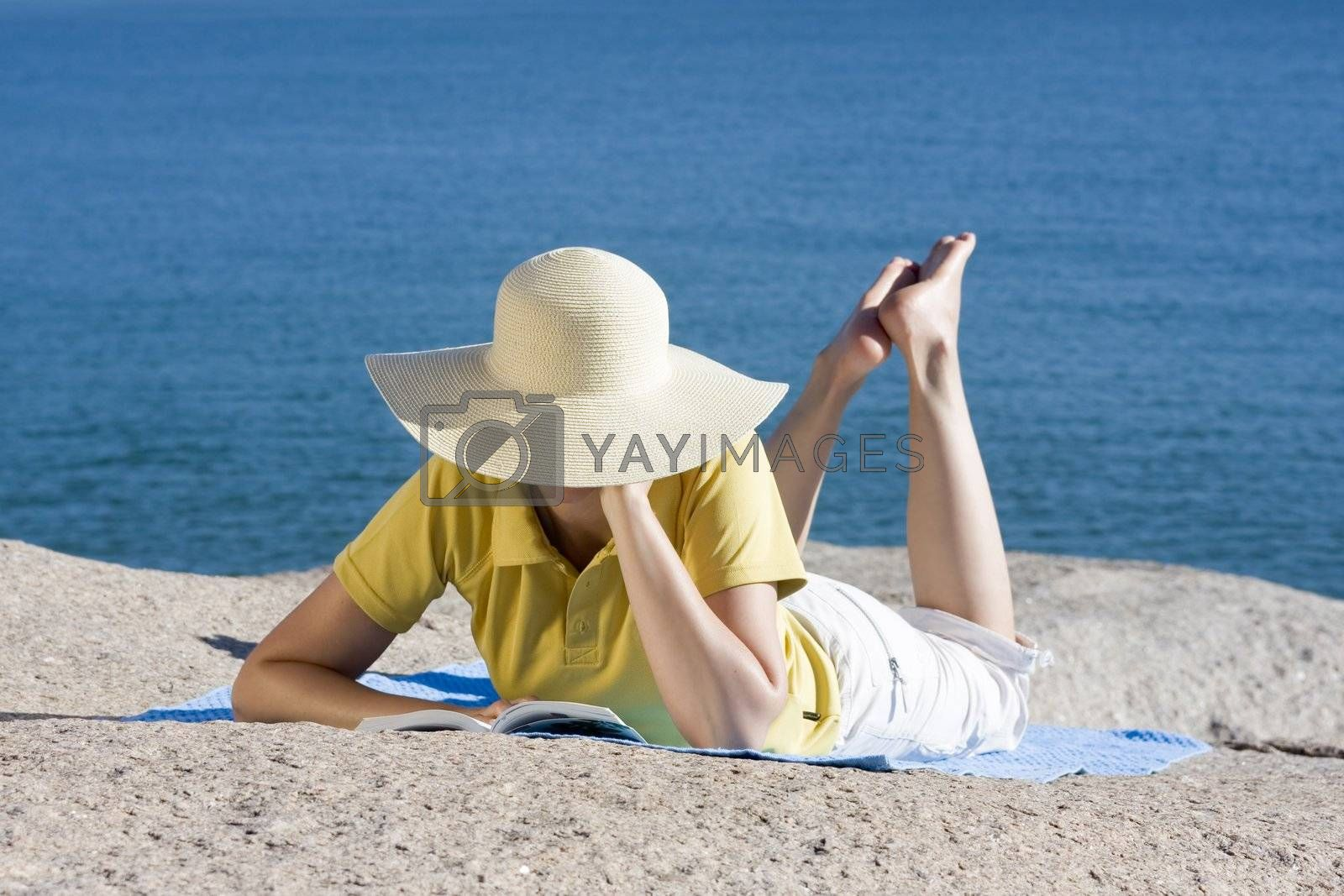 Woman reading a book at the sea by ArtmannWitte