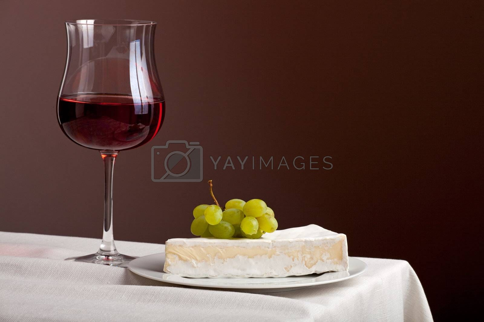 glass of red wine and camembert cheese with grapes by bernjuer