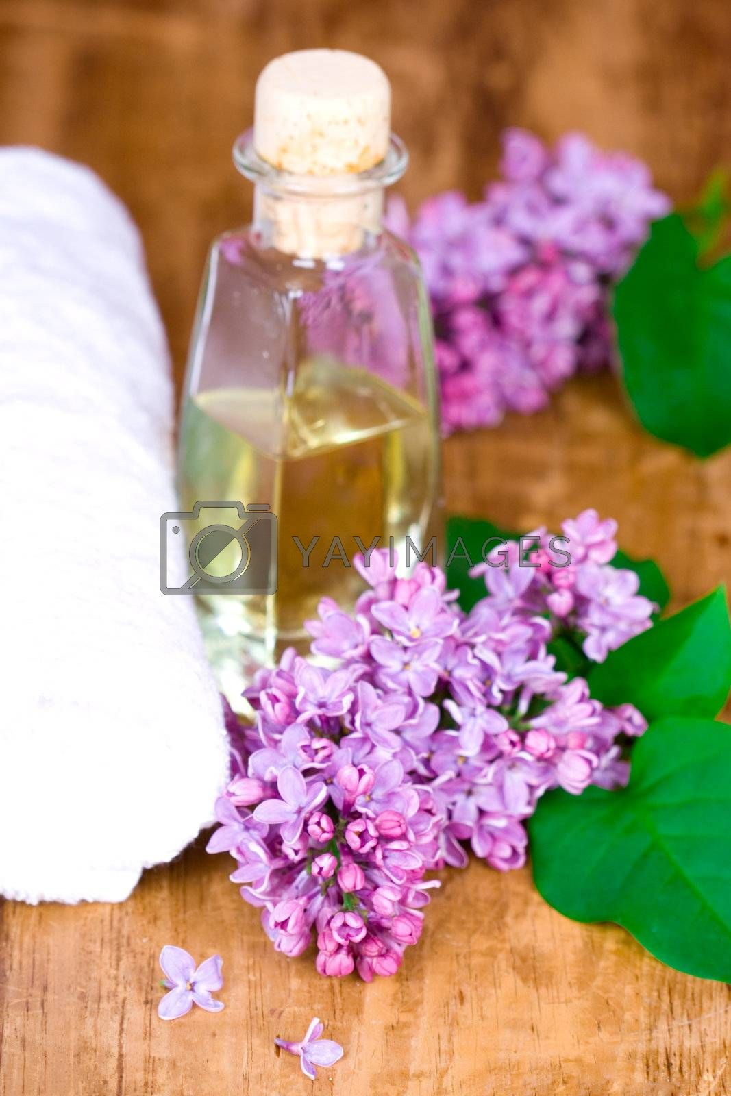 bath and spa items (towel, oil, lilac) on wooden background