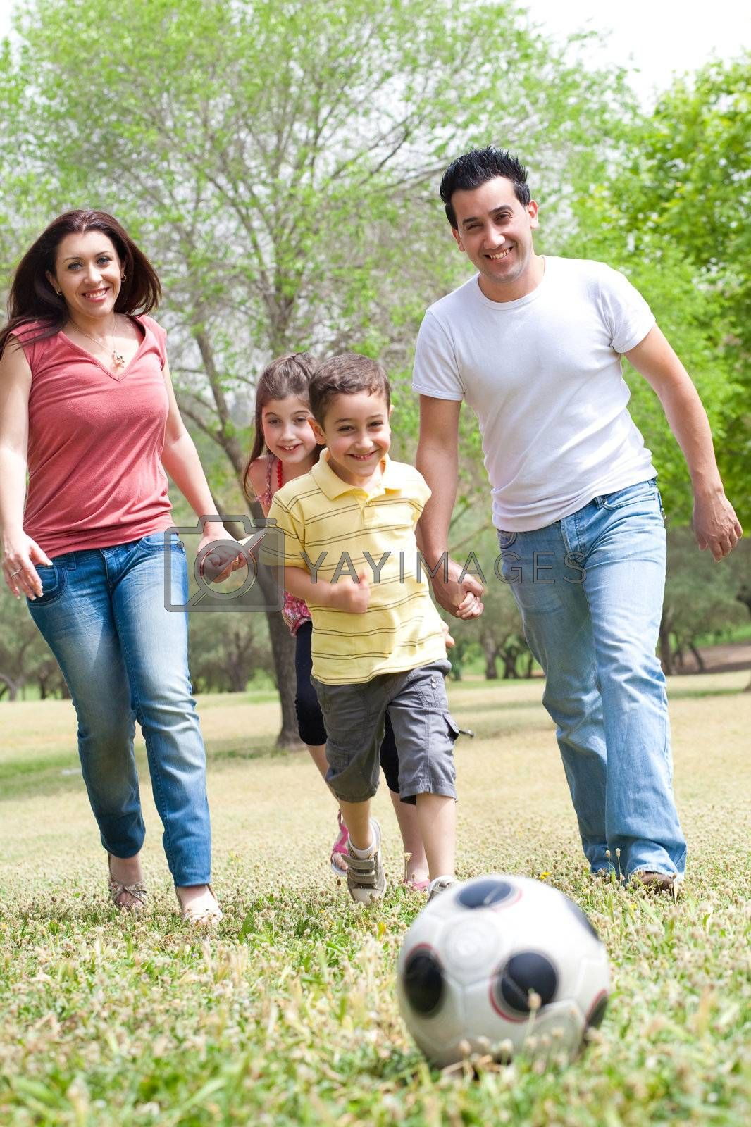 Family outdoor playing soccer and having fun