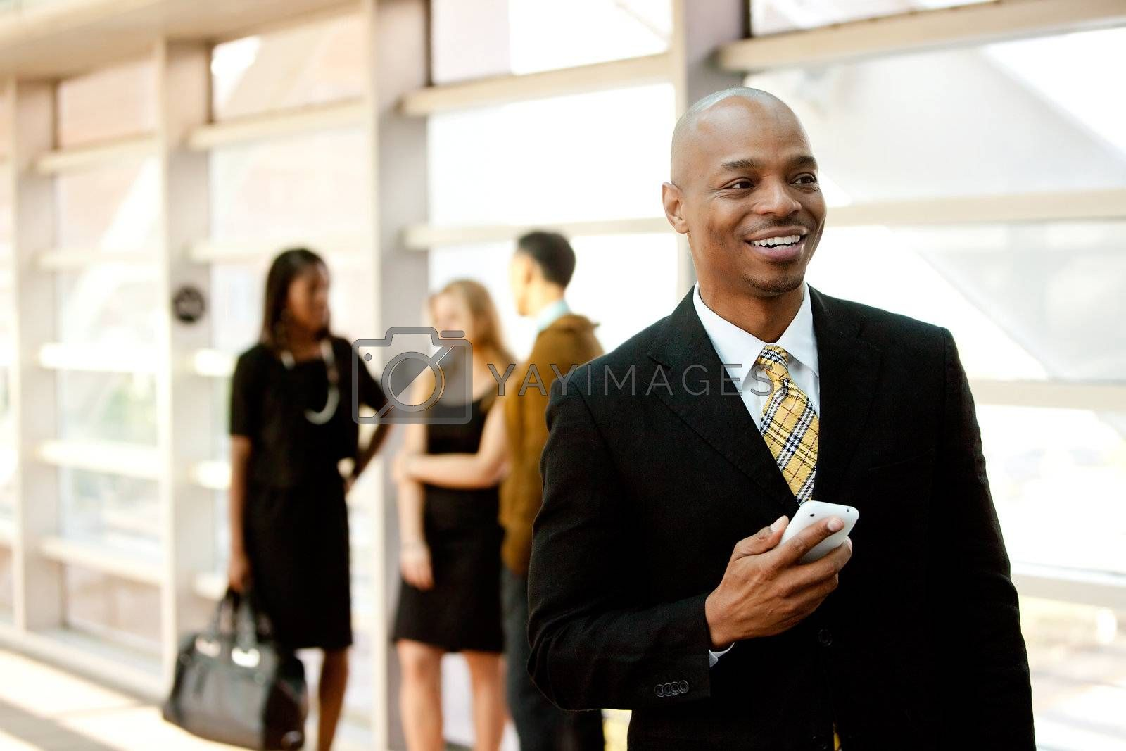 A business man with a smart phone and co-workers in the background