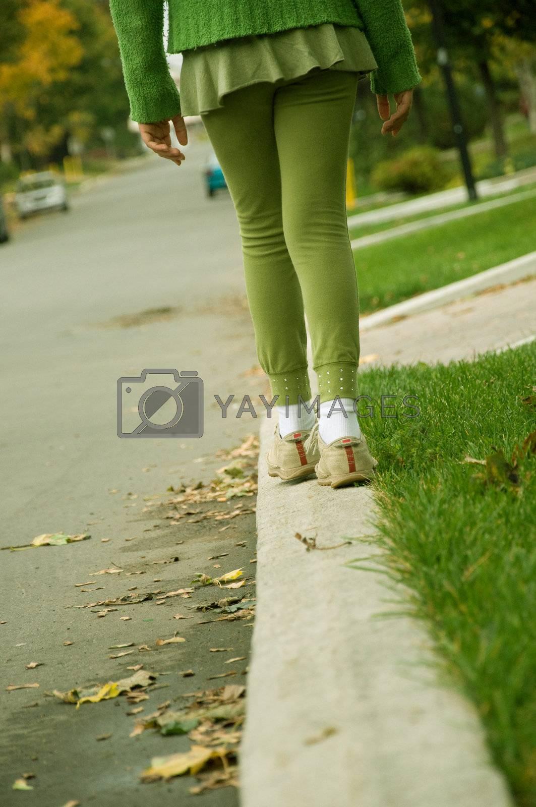 A girl balancing her self on the sidewalk.