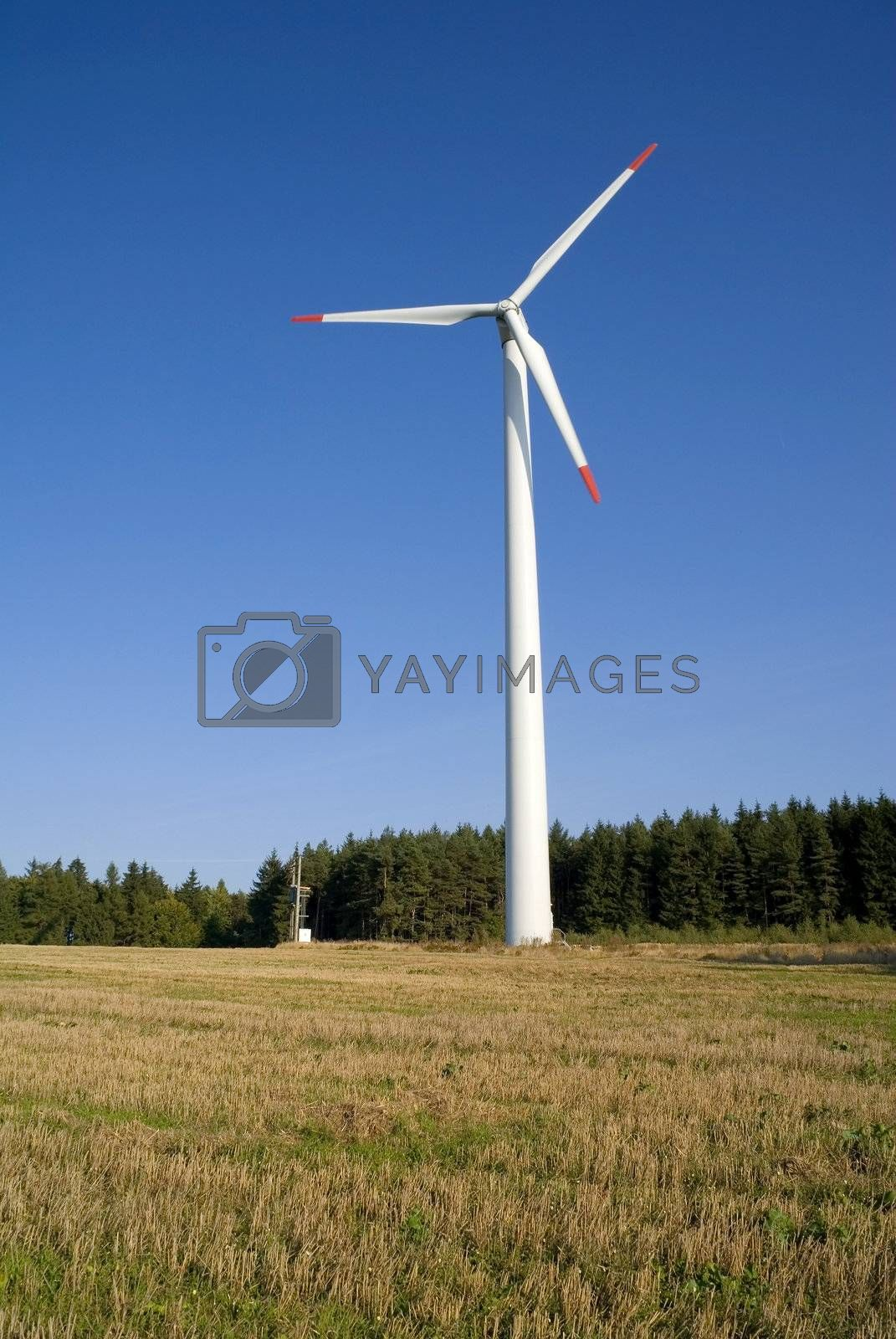 Wind turbine against blue sky with the forest in background