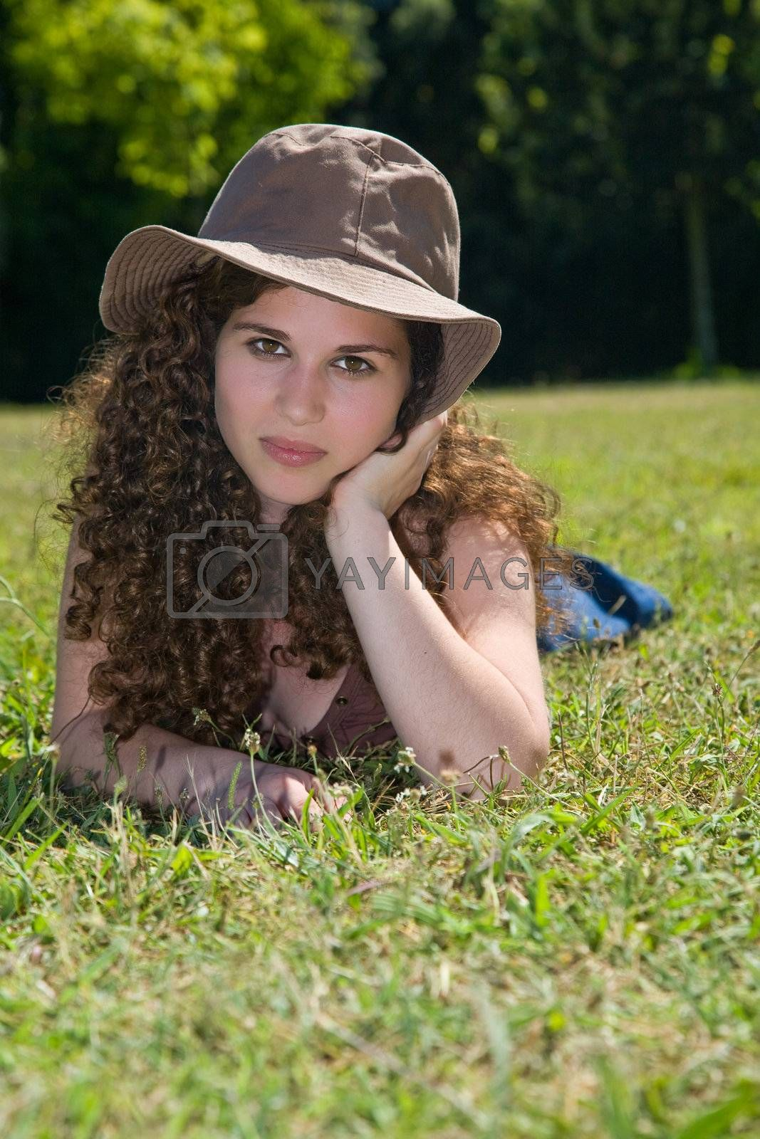Pretty young girl with a hat, laying down in the grass on a park.
