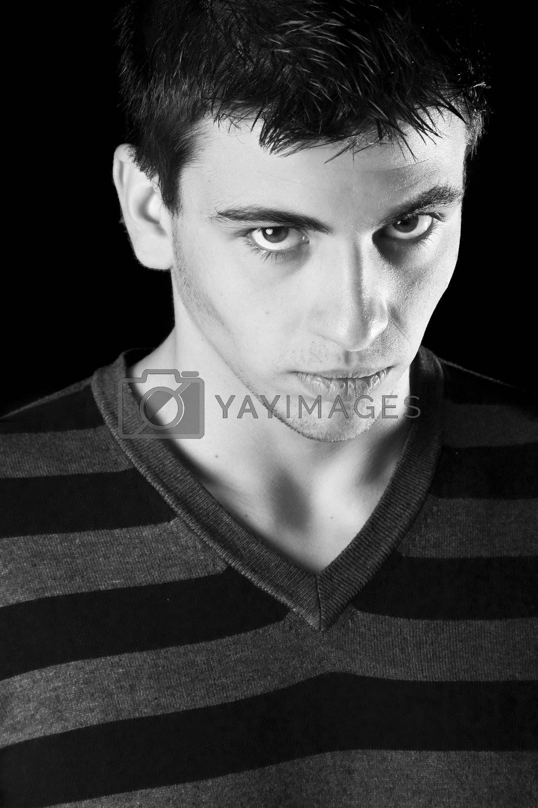 Black and white portrait of a young boy with a tough expression.