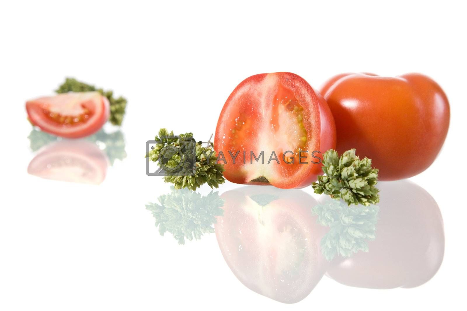 Tomatoes and oregano leafs, isolated on white background.