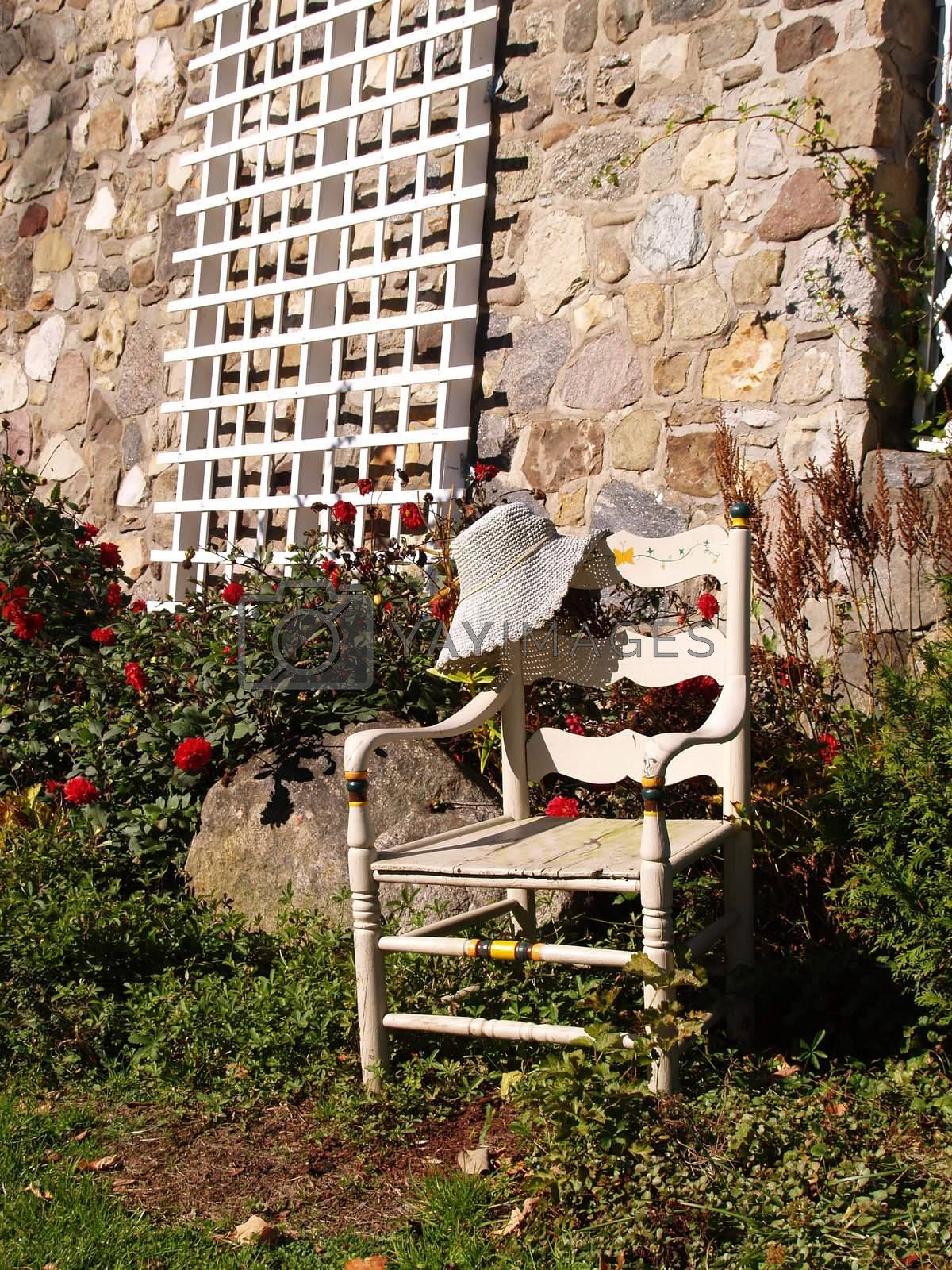 empty white chair outdoors by a stone building